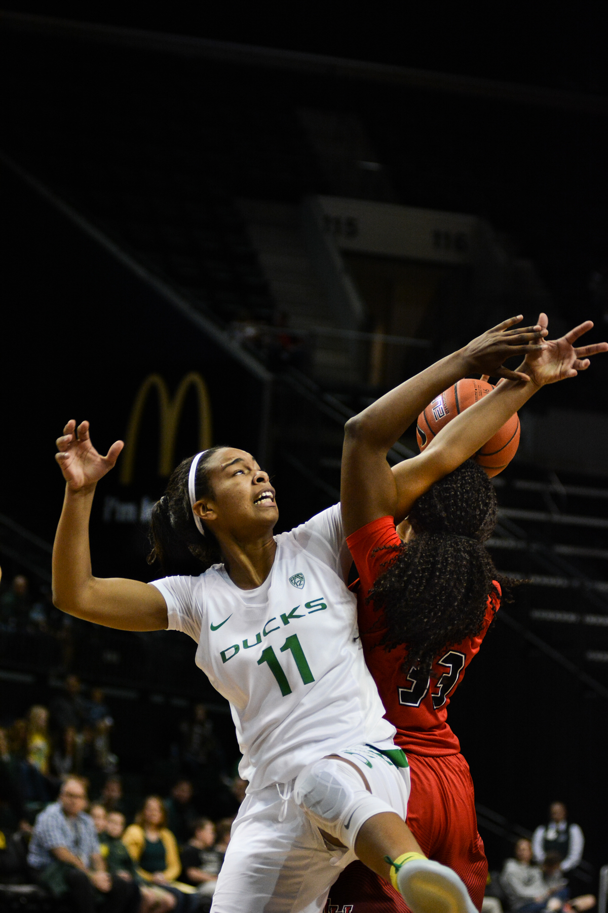 Ducks Jayde Woods (#11) and Cardinals Kiandra Bowers (#33) battle in the air over a loose ball. The Oregon Ducks women's basketball team won their season opener against the Lamar Cardinals 84-67. Photo by Jacob Smith, Oregon News Lab