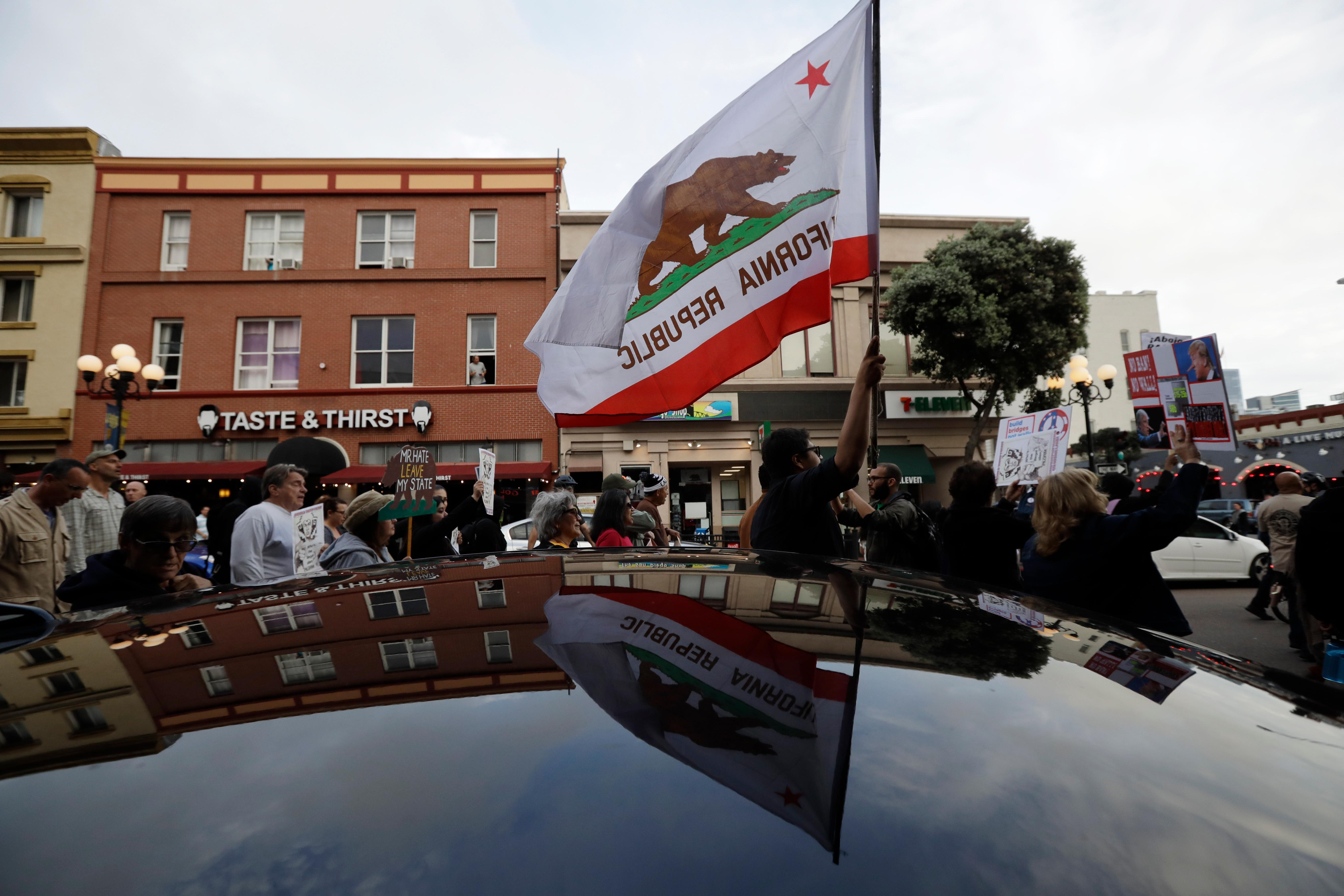 People march during a rally against a scheduled upcoming visit by President Donald Trump, Monday, March 12, 2018, in San Diego. Trump is scheduled to visit San Diego, Tuesday, setting foot in California for his first time as president. (AP Photo/Gregory Bull)