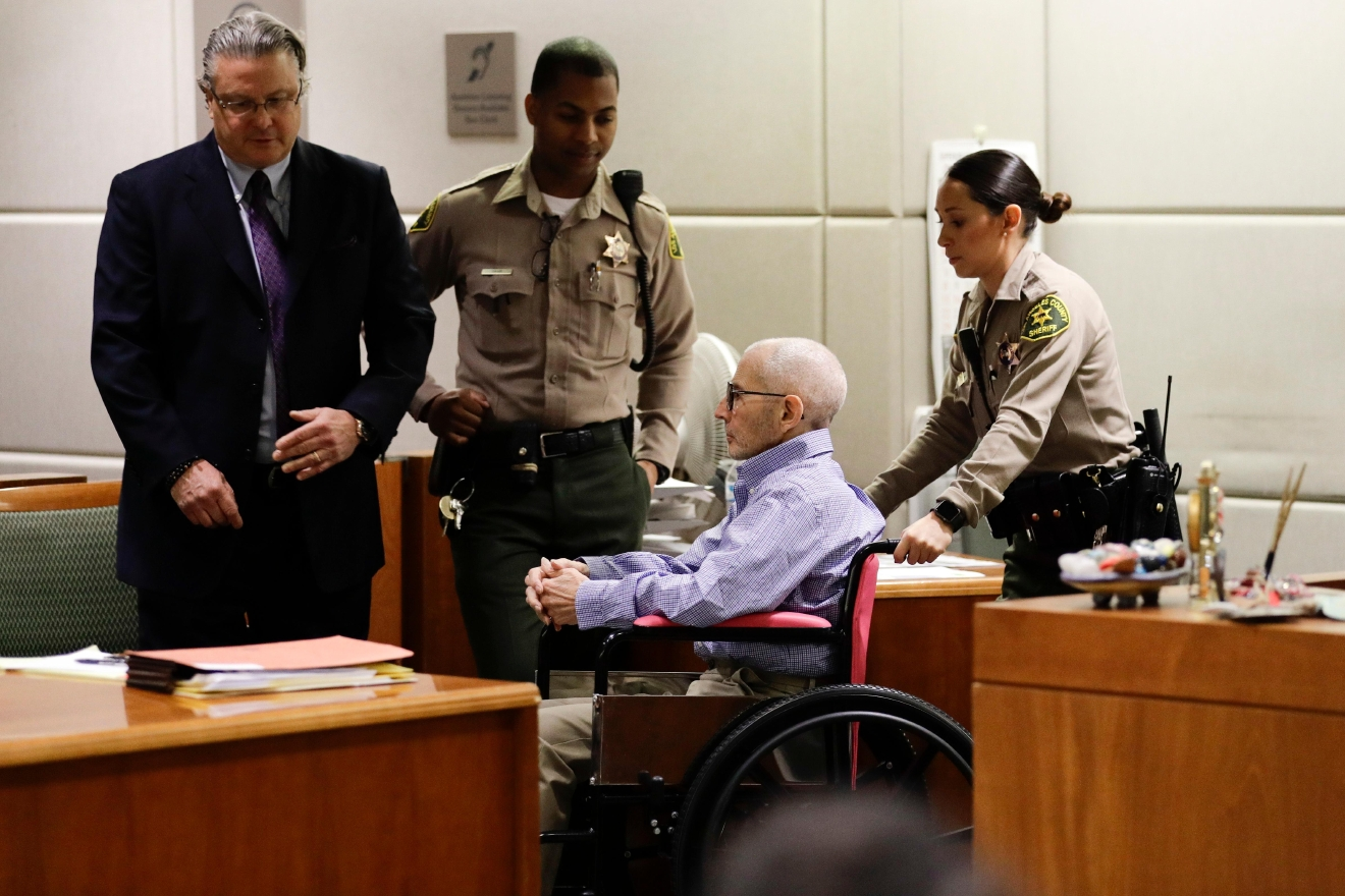Real estate heir Robert Durst, center, is brought into a courtroom in the wheelchair for a hearing Wednesday, Dec. 21, 2016, in Los Angeles. At left is his attorney David Chesnoff. (AP Photo/Jae C. Hong, Pool)