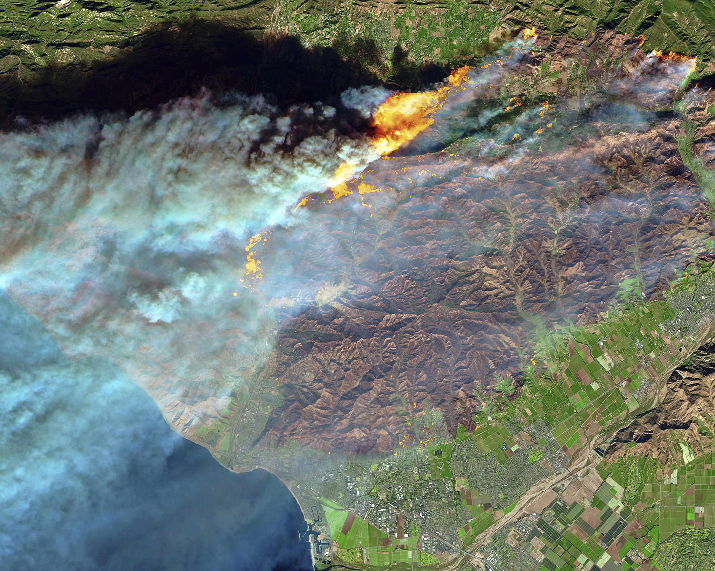 FILE - This Thursday, Dec. 7, 2017 false-color image from the European Space Agency's Sentinel-2 satellite via NASA, shows a brown burn scar from the Thomas fire north of the city of Ventura, Calif., at bottom center. The flames stand out starkly as smoke billows toward the Pacific Ocean and untouched areas of vegetation appear in bright shades of green. The huge wildfire that burned hundreds of homes in Santa Barbara and Ventura counties is now the largest in California's recorded history. State fire officials said Friday, Dec. 22, 2017, that the Thomas fire has scorched 273,400 acres, or about 427 square miles of coastal foothills and national forest. (European Space Agency/NASA via AP, File)