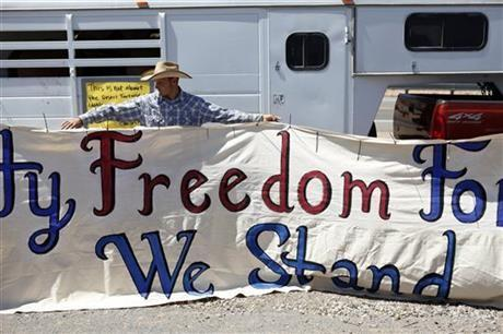 John Banks holds up a banner during a rally in support of Cliven Bundy near Bunkerville Nev. Monday, April 7, 2014, 2014.