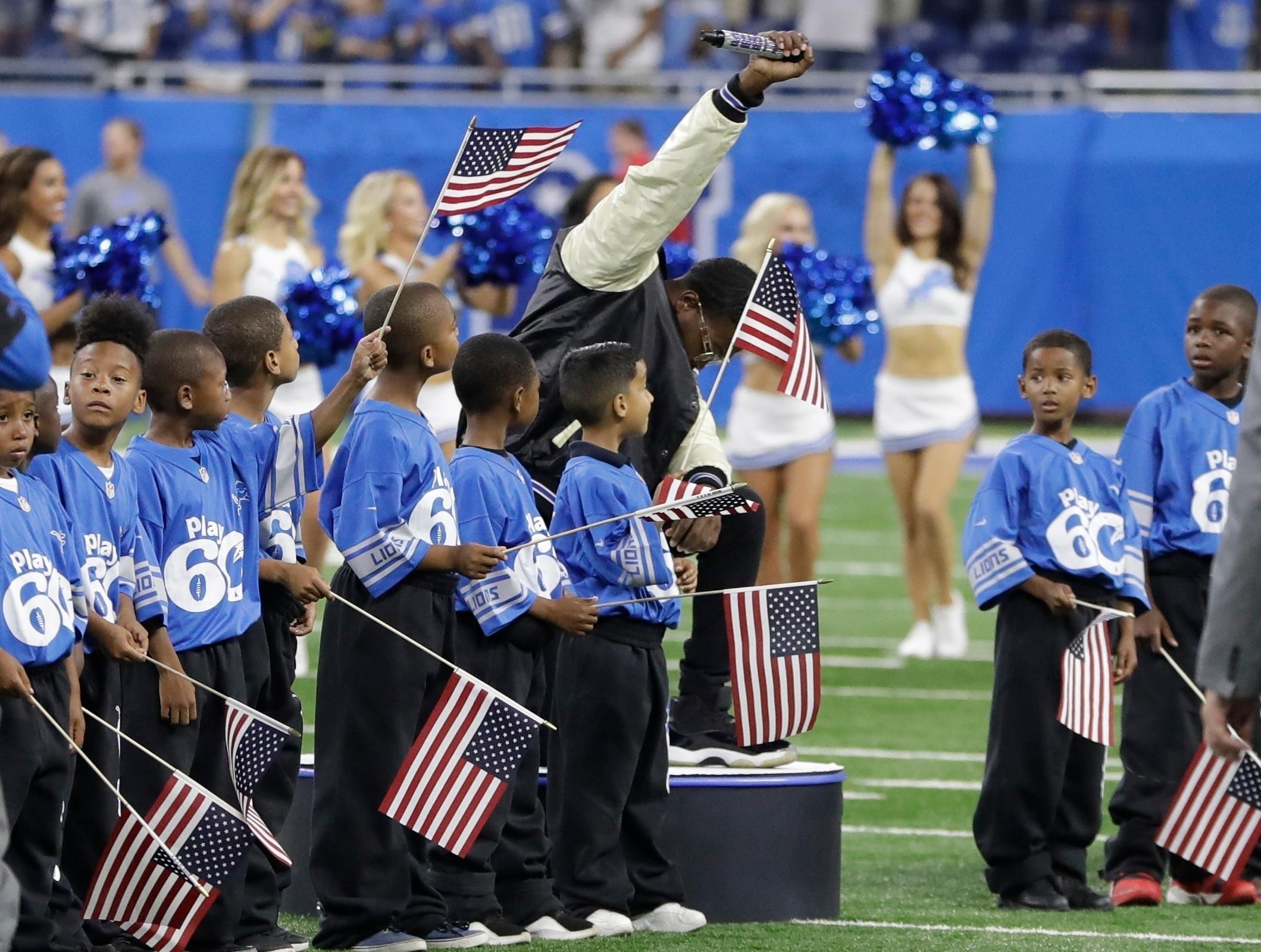 "FILE- In a file photo from Sept. 24, 2017, National anthem singer Rico Lavelle bends to his knee, bows his head and raises his fist after singing the anthem before the first half of an NFL football game between the Detroit Lions and the Atlanta Falcons in Detroit. The sight of football players kneeling during the national anthem is the continuation of a tradition nearly as old the song itself. University of Michigan musicology professor Mark Clague says ""The Star-Spangled Banner"" has been a channel for protest since at least the 1840s. The lyrics were recast as an anti-slavery song and it's been used or reworked to push for racial equality, women's suffrage, prohibition and labor rights. (AP Photo/Carlos Osorio, File)"
