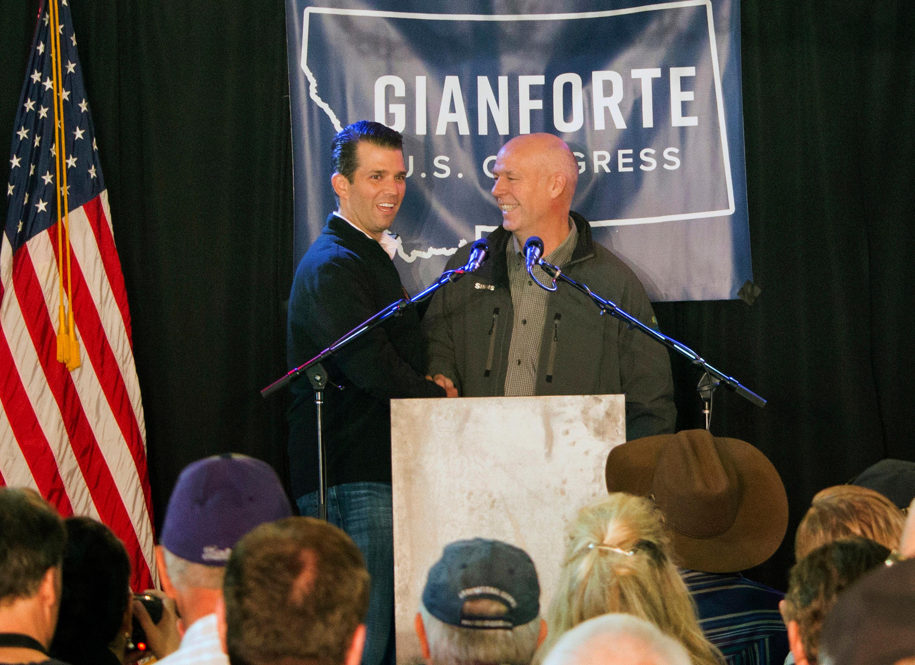 FILE - In this May 11, 2017, file photo Republican Greg Gianforte, right, welcomes Donald Trump Jr., the U.S. president's son, onto the stage at a rally in East Helena, Mont. Gianforte won Montana's only U.S. House seat on Thursday, May 25, despite being charged a day earlier with assault after witnesses said he grabbed a reporter by the neck and threw him to the ground. (AP Photo/Bobby Caina Calvan, File)