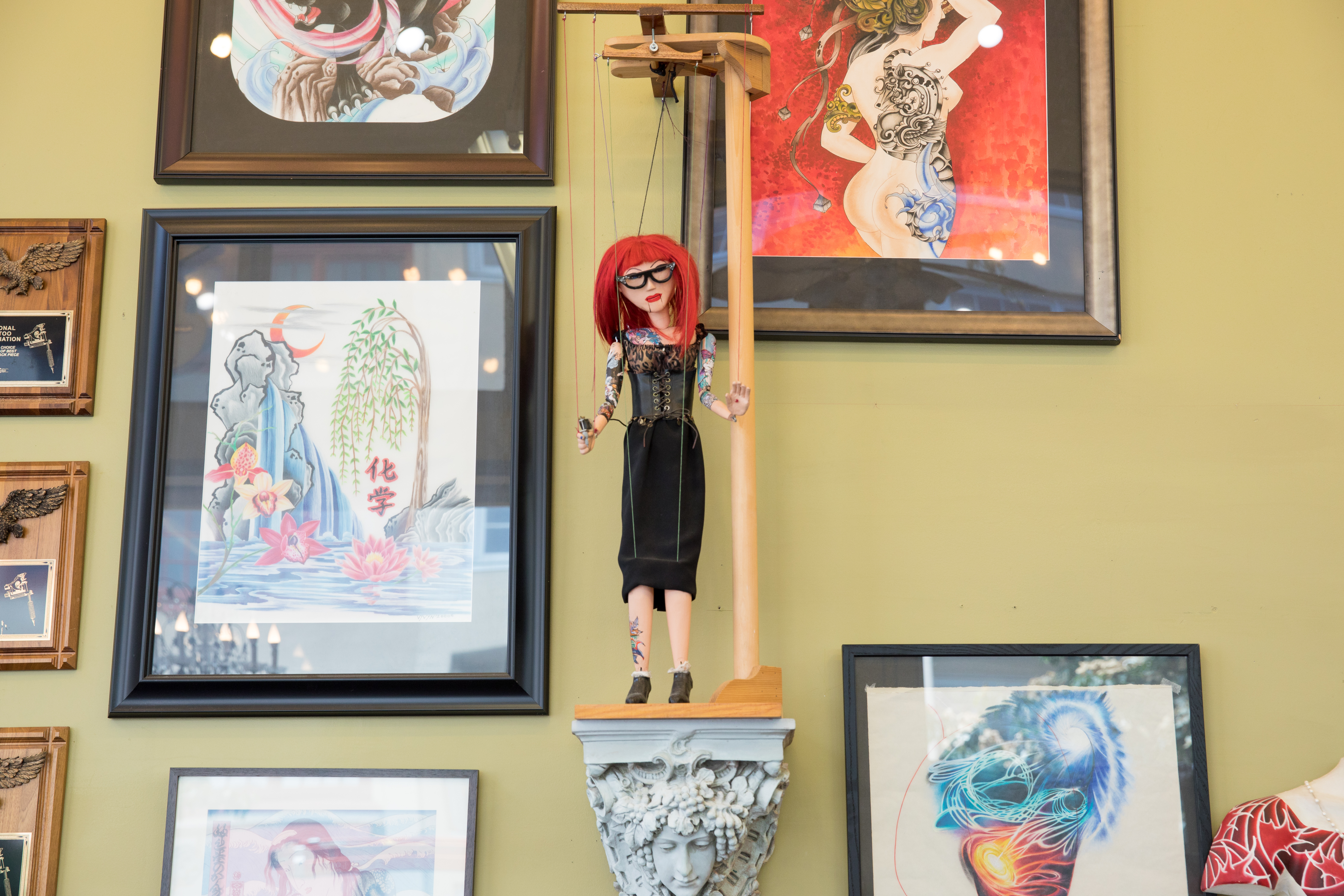 "A red-haried marionette doll made in the likeness of Vyvyn ""Madame"" Lazonga greets visitors who enter Madame Lazonga's Tattoo. Made by an ex-boyfriend of Vyvyn's, the doll is an exact image of the artist in her younger years, down to the tattoos painted on her arms. (Image: Riley Bunch / Seattle Refined)"