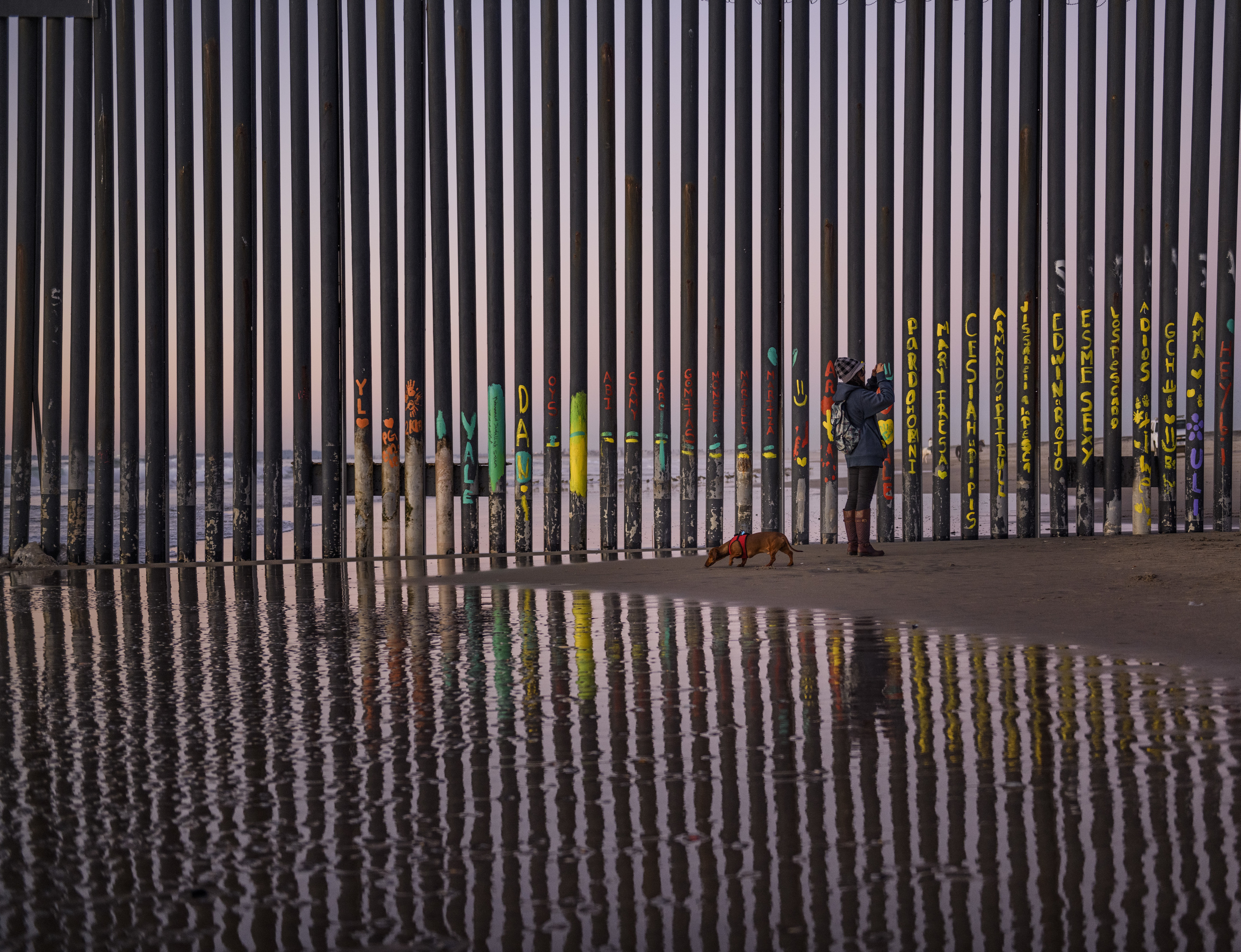 FILE - In this Jan. 3, 2019, file photo, a woman takes a snapshot by the border fence between San Diego, Calif., and Tijuana, as seen from Mexico. (AP Photo/Daniel Ochoa de Olza, File)