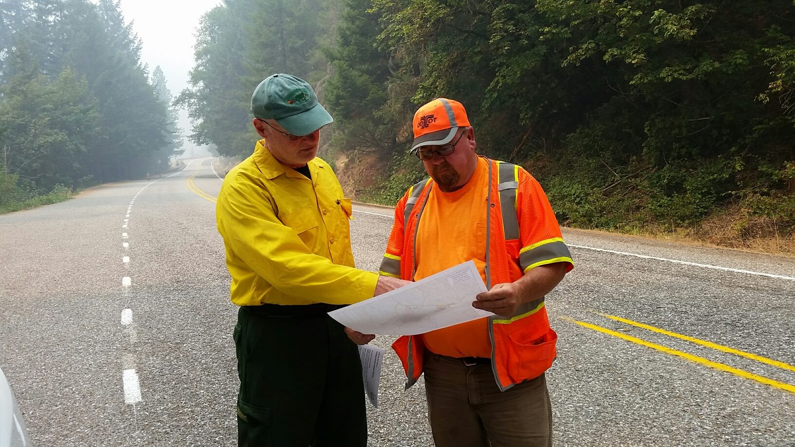 Public Information Officer Dee Hines explains a closure map to an ODOT employee on Highway 138, east of Glide. (Photo courtesy US Forest Service-Umpqua National Forest)