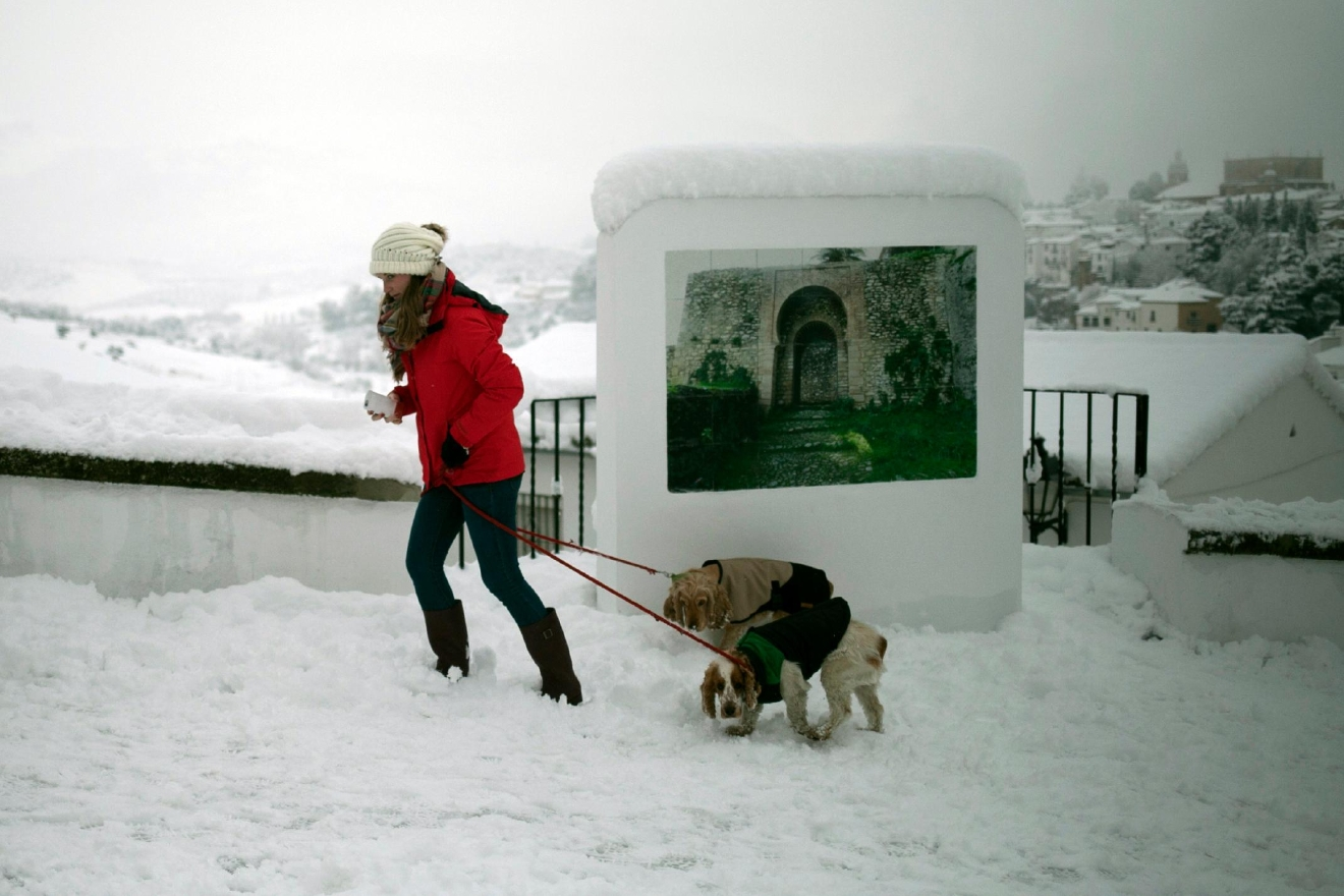 A woman walks with her dogs through a street after snowfall in the city of Ronda, southern Spain, Thursday, Jan. 19, 2017.  (AP Photo/Javier Gonzalez)