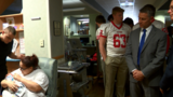 Scholar football players and UT's Candle meet with Mercy Children's patients