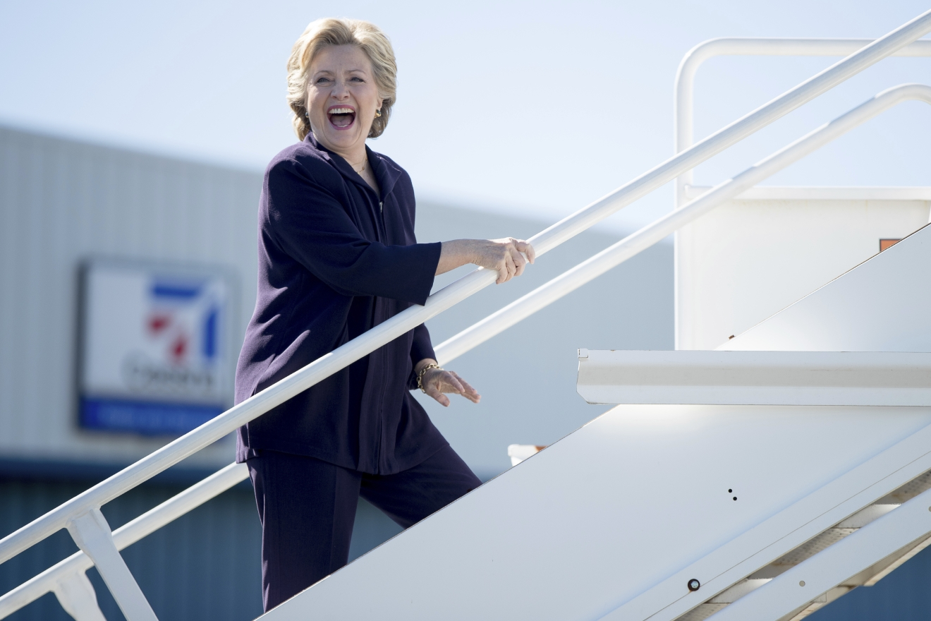 Democratic presidential candidate Hillary Clinton laughs as she answers a reporters question while boarding her campaign plane in White Plains, N.Y., Monday, Oct. 10, 2016, to travel to Detroit. (AP Photo/Andrew Harnik)