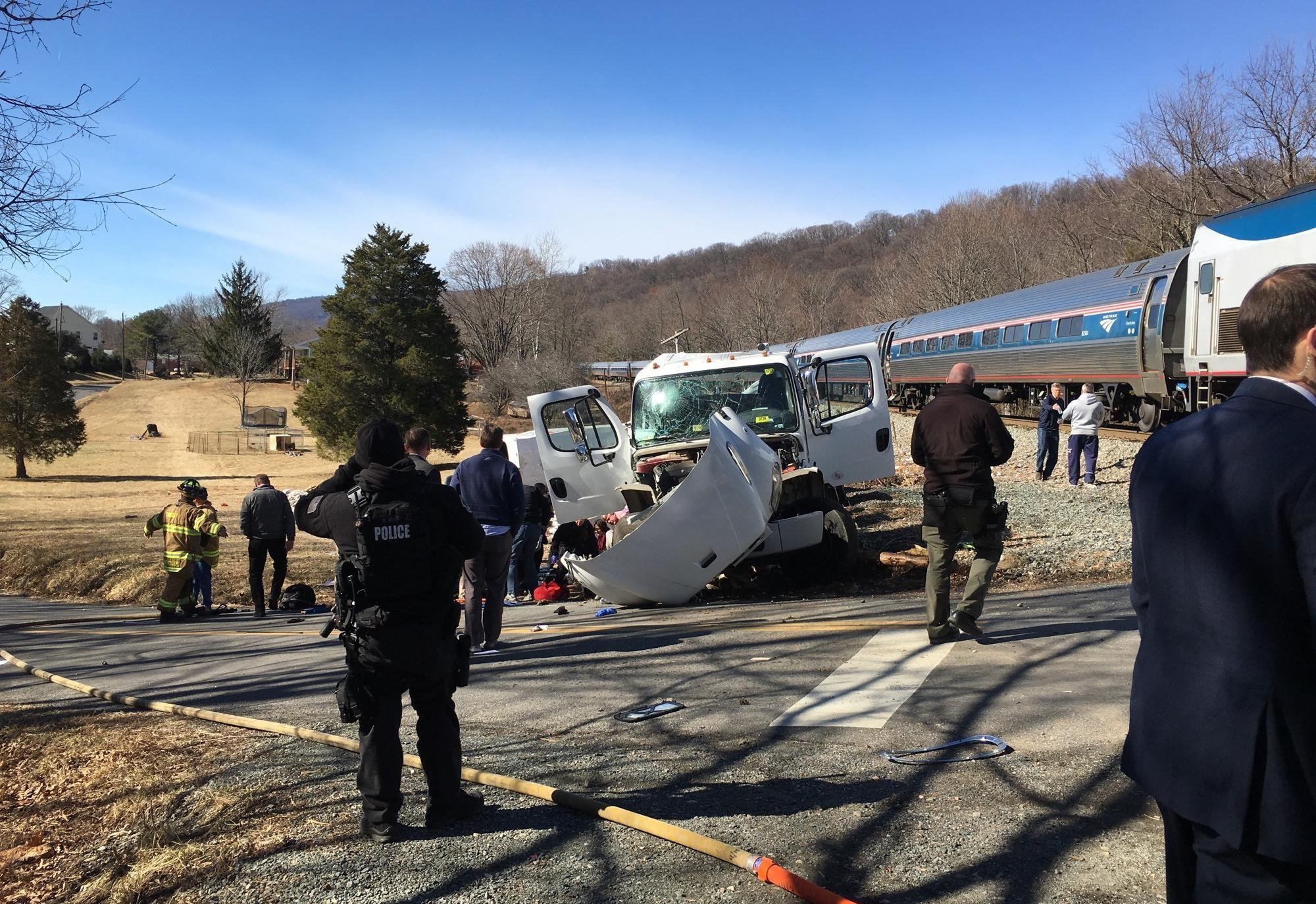 This photo provided by Rep. Bruce Poliquin, R-Maine shows emergency personnel standing near a chartered train carrying members of Congress after it hit a garbage truck in Crozet, Va., Wednesday, Jan. 31, 2018.  No lawmakers were believed injured.  (Bruce Poliquin via AP)