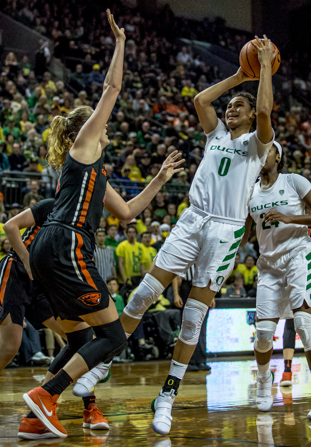 Oregon forward Satou Salby (#0) shoots over Oregon State center Marie Gülich (#21). The Oregon Ducks defeated the Oregon State Beavers 75-63 on Sunday afternoon in front of a crowd of 7,249 at Matthew Knight Arena. The Ducks and Beavers split the two game Civil War with the Beavers defeating the Ducks on Friday night in Corvallis. The Ducks had four players in double digits: Satou Sabally with 21 points, Maite Cazorla with 16, Sabrina Ionescu with 15, and Mallory McGwire with 14. The Ducks shot 48.4% from the floor compared to the Beavers 37.3%. The Ducks are now 7-1 in conference play. Photo by Ben Lonergan, Oregon News Lab
