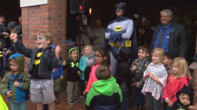 Professional Batman Clint Young stands with a group of children for a photo on Tuesday in downtown Walla Walla for the first-ever Adam West Day.