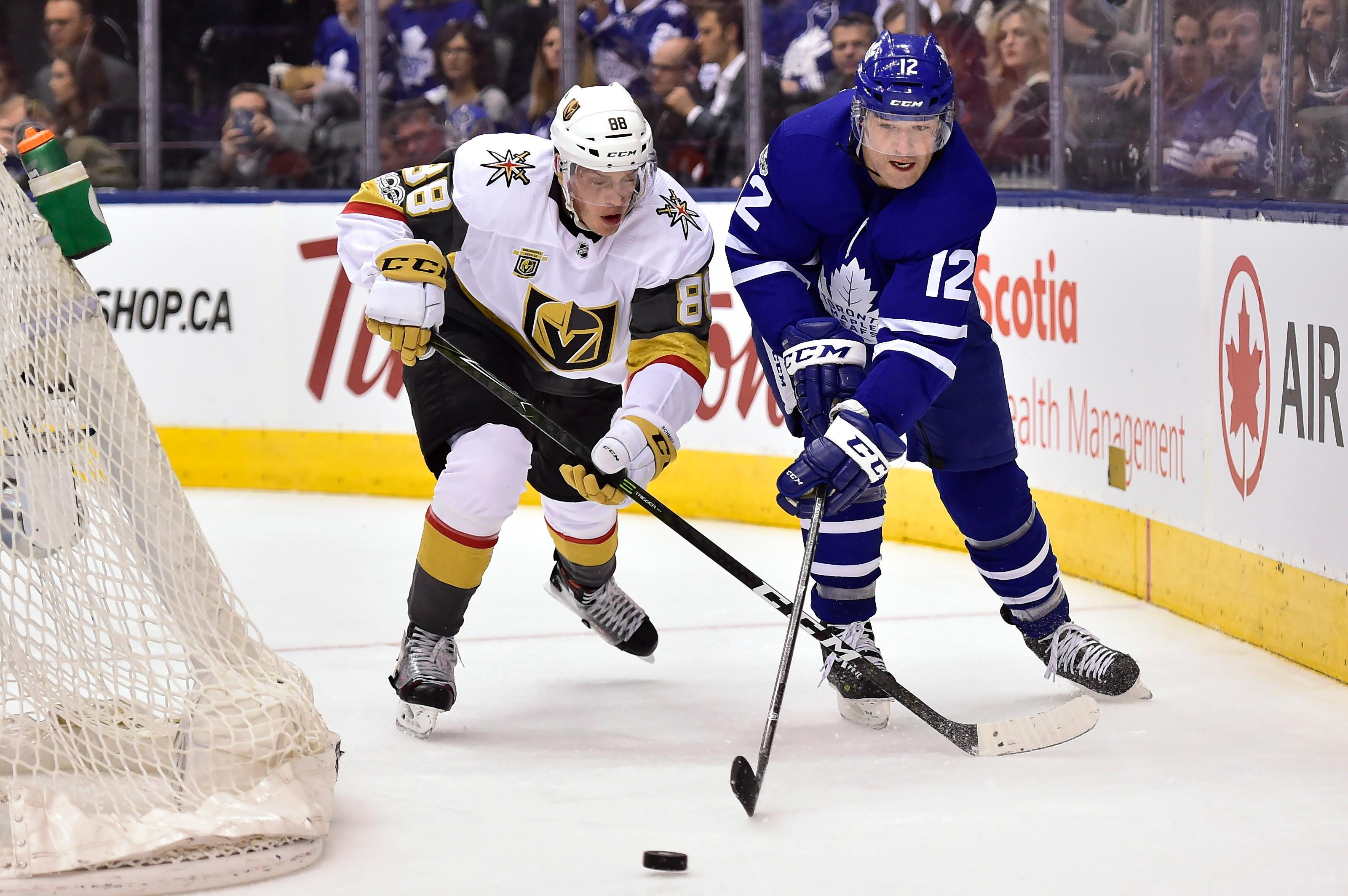 Toronto Maple Leafs center Patrick Marleau (12) and Vegas Golden Knights defenseman Nate Schmidt (88) battle for the puck behind the net during the second period of an NHL hockey game, Monday, Nov. 6, 2017, in Toronto. (Frank Gunn/The Canadian Press via AP)