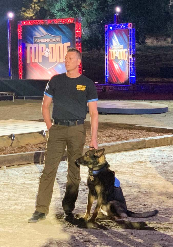 "Deputy Todd Thompson and his K9 partner, Eddy, strike a pose on the set of ""America's Top Dog."" Photo via Mitch Talley."