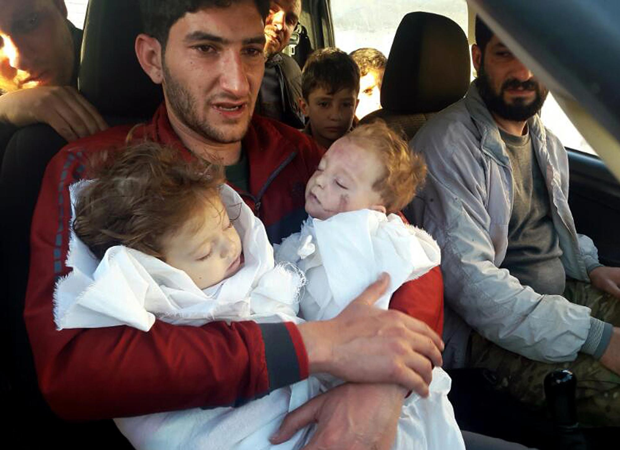 FILE -- In this Tuesday April 4, 2017 file photo, Abdel Hameed Alyousef, 29, holds his twin babies who were killed during a suspected chemical weapons attack, in Khan Sheikhoun in the northern province of Idlib, Syria. Turkey's health minister, Recep Akdag said Tuesday, April 11, 2017, that test results conducted on victims of the chemical attack in Khan Sheikhoun confirm that sarin gas was used. Officials from the World Health Organization and the Organization for the Prohibition of Chemical Weapons participated in the autopsies. (Alaa Alyousef via AP, File)