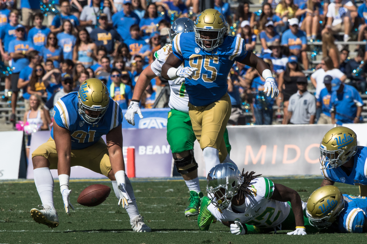 UCLA defensive lineman Jacob Tuioti-Mariner (#91) scoops up an Oregon fumble. The Oregon Ducks rallied during the second quarter to go into halftime tied 14-14 with the UCLA Bruins at Rose Bowl Stadium in Pasadena, California. Photo by Austin Hicks, Oregon News Lab