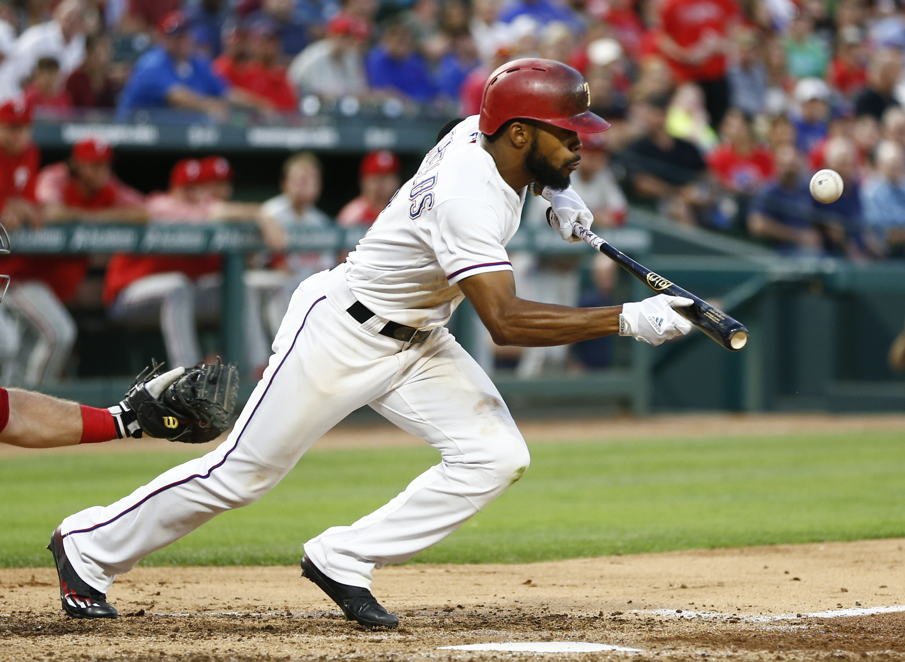 Texas Rangers left fielder Delino DeShields bunts for a single against the Philadelphia Phillies during the third inning of a baseball game, Wednesday, May 17, 2017, in Arlington, Texas. (AP Photo/Jim Cowsert)