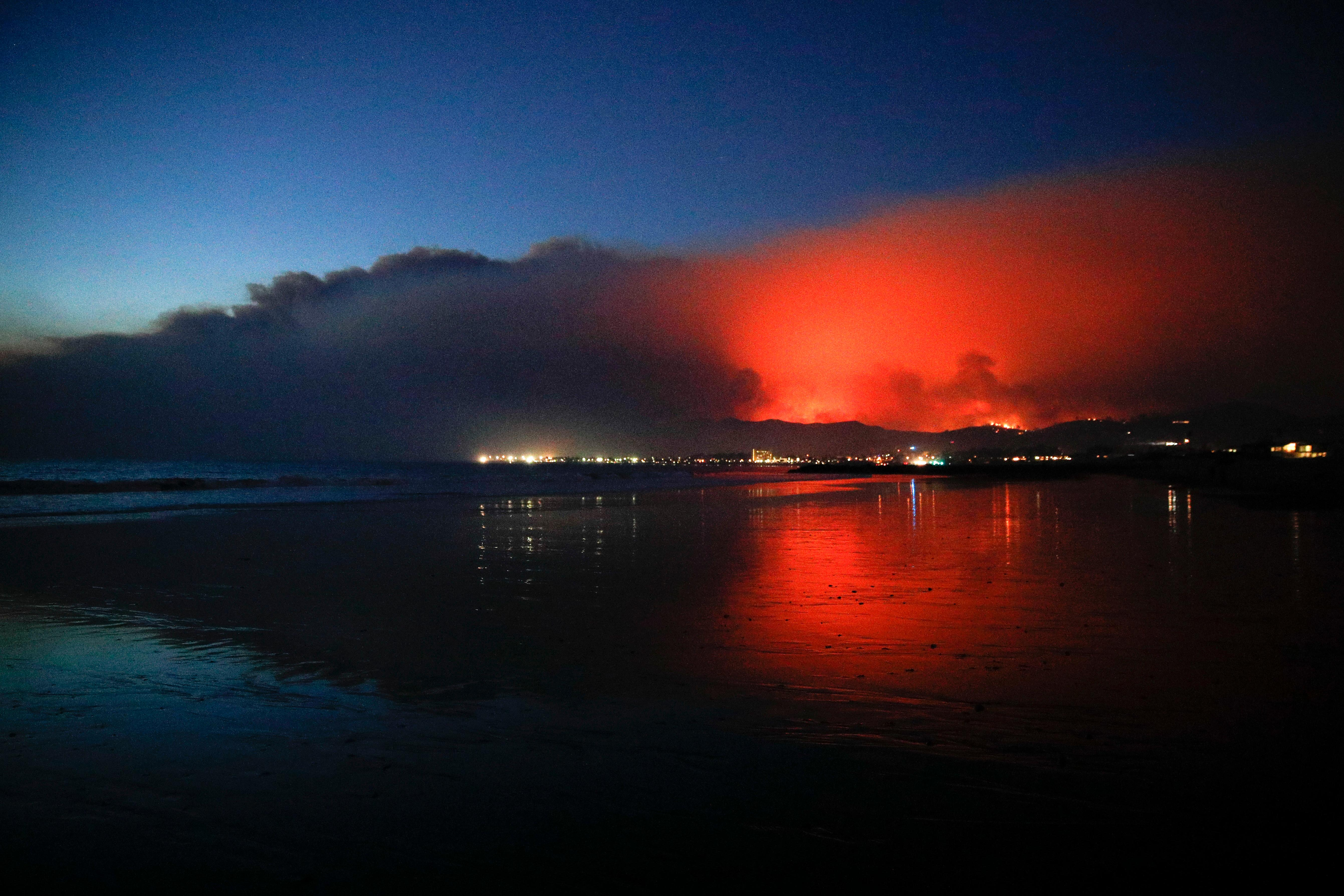 A wildfire continues to burn as its red glow is reflected on the beach Tuesday, Dec. 5, 2017, in Ventura, Calif. Raked by ferocious Santa Ana winds, explosive wildfires northwest of Los Angeles and in the city's foothills burned a psychiatric hospital and scores of homes Tuesday and forced the evacuation of tens of thousands of people. (AP Photo/Jae C. Hong)