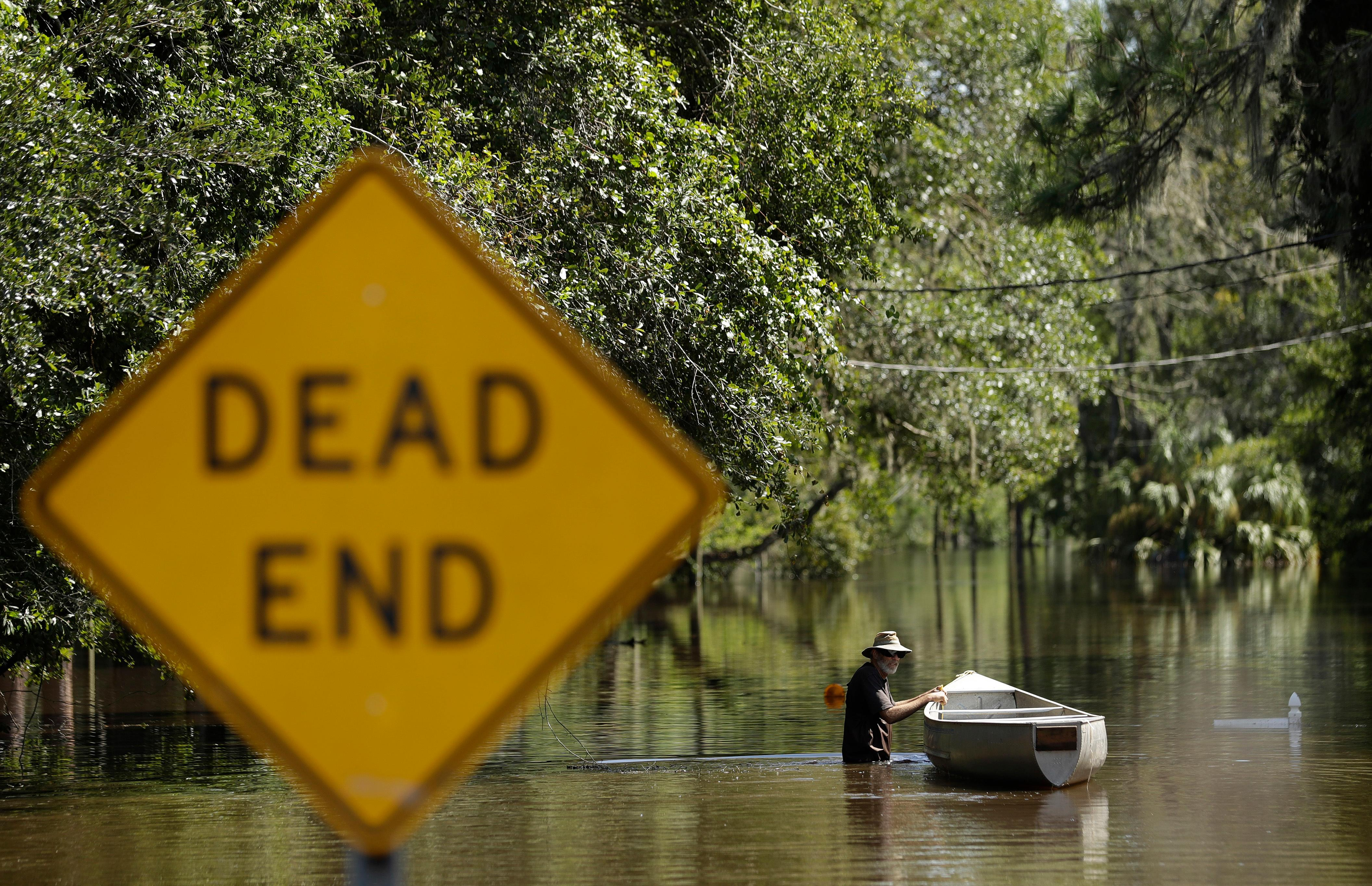 A man, who refused to be identified, pushes a canoe through water from the Alafia River Tuesday, Sept. 12, 2017, in Lithia, Fla. A storm surge from Hurricane Irma pushed water into the low lying area. (AP Photo/Chris O'Meara)