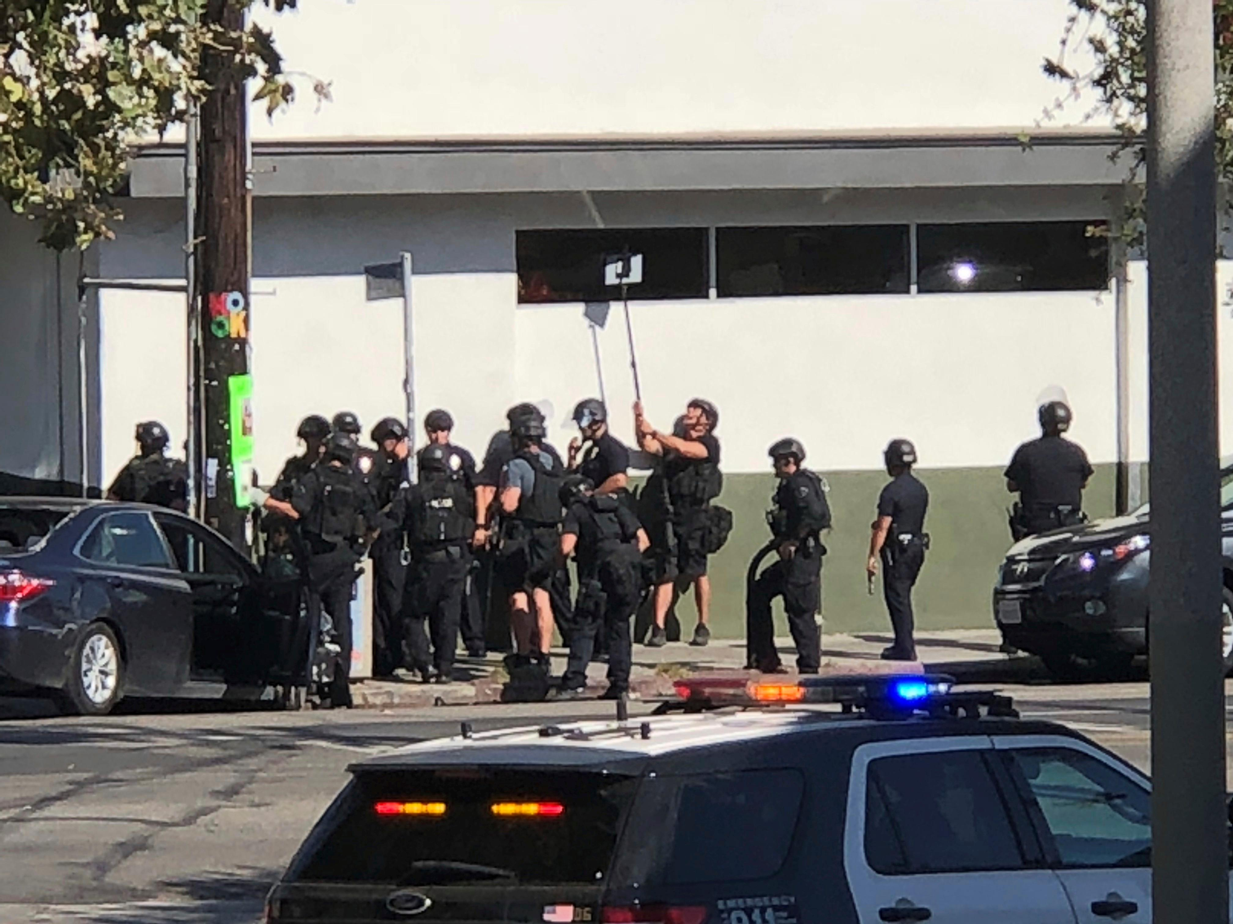 In this photo provided by Christian Dunlop, police officers use a mirror to see inside a Trader Joe's store in the Silver Lake neighborhood of Los Angeles on Saturday, July 21, 2018. Police believe a man involved in the standoff with officers shot his grandmother and girlfriend before firing at officers during a pursuit, then crashing outside the supermarket and running inside the store. (Christian Dunlop via AP)