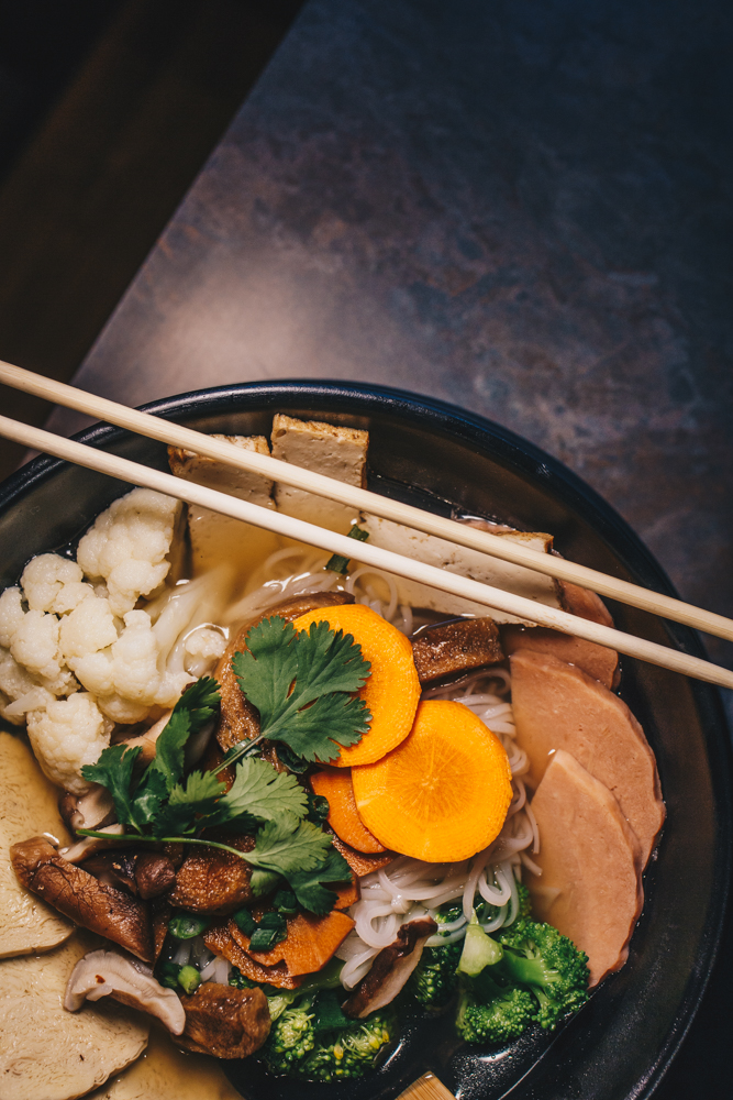 "Cleansing noodle soup: savory honeydew vegetable broth with vegan mock ham, gluten ""meats"", tofu, cauliflower, broccoli, daikon, and carrots served with rice noodles and topped with green onions / Image: Catherine Viox // Published: 4.22.19"