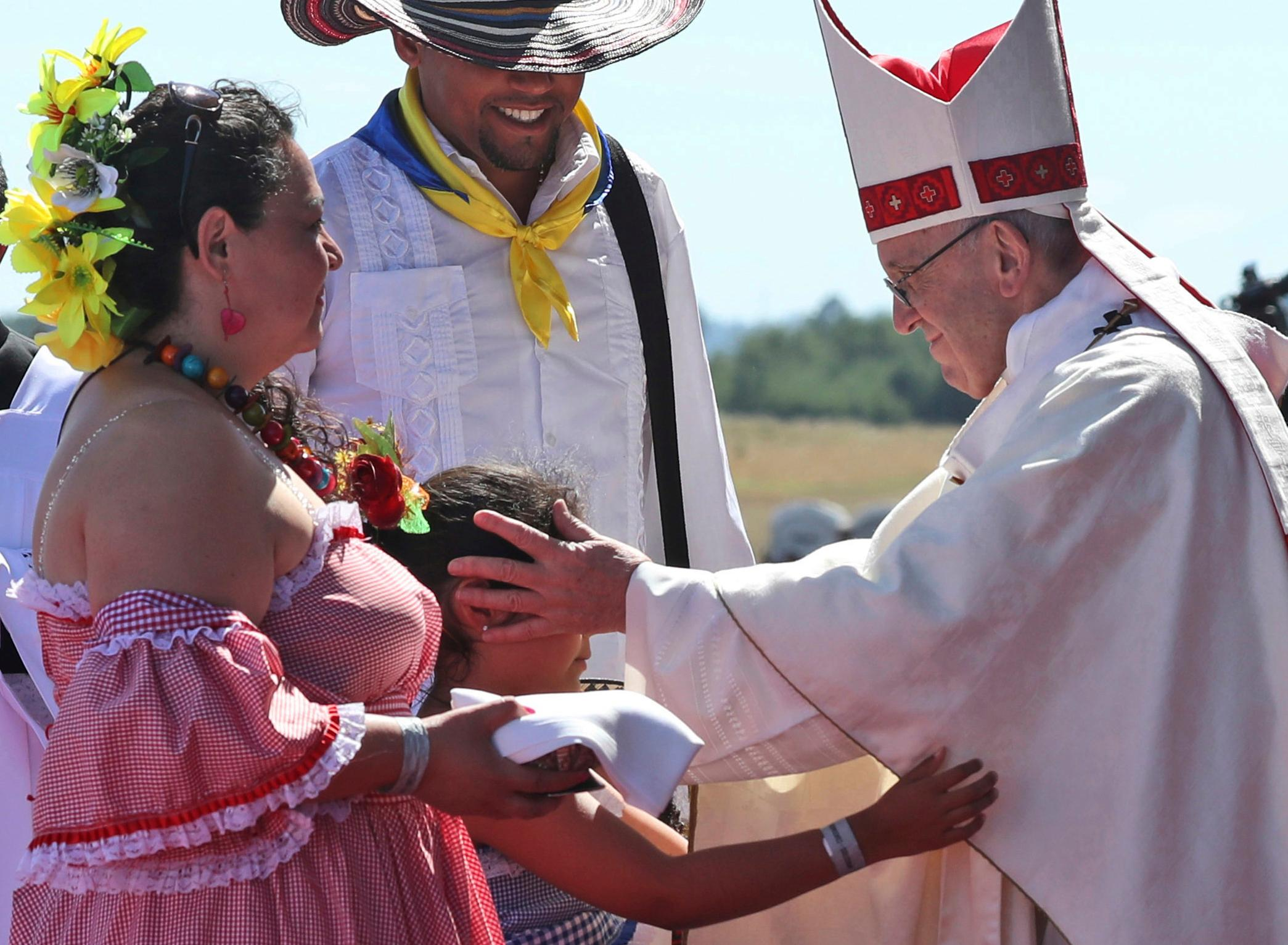 "ALTERNATIVE CROP TO ALT114 -  A child reaches out to embrace Pope Francis in the offertory of a Mass at the Maquehue Air Base, in Temuco, Chile, Wednesday, Jan. 17, 2018. Francis is paying homage to Chileans who were tortured or killed at the air base. Francis said the area is ""the site of grave violations of human rights,"" and that the Mass was being offered for all those who have suffered or died. (AP Photo/Alessandra Tarantino)"