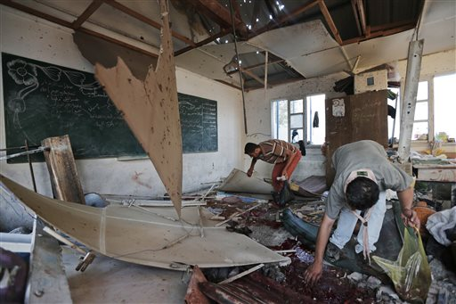 Palestinians collect body parts in a classroom at the Abu Hussein U.N. school in Jebaliya refugee camp, northern Gaza Strip, which was hit by an Israeli strike.