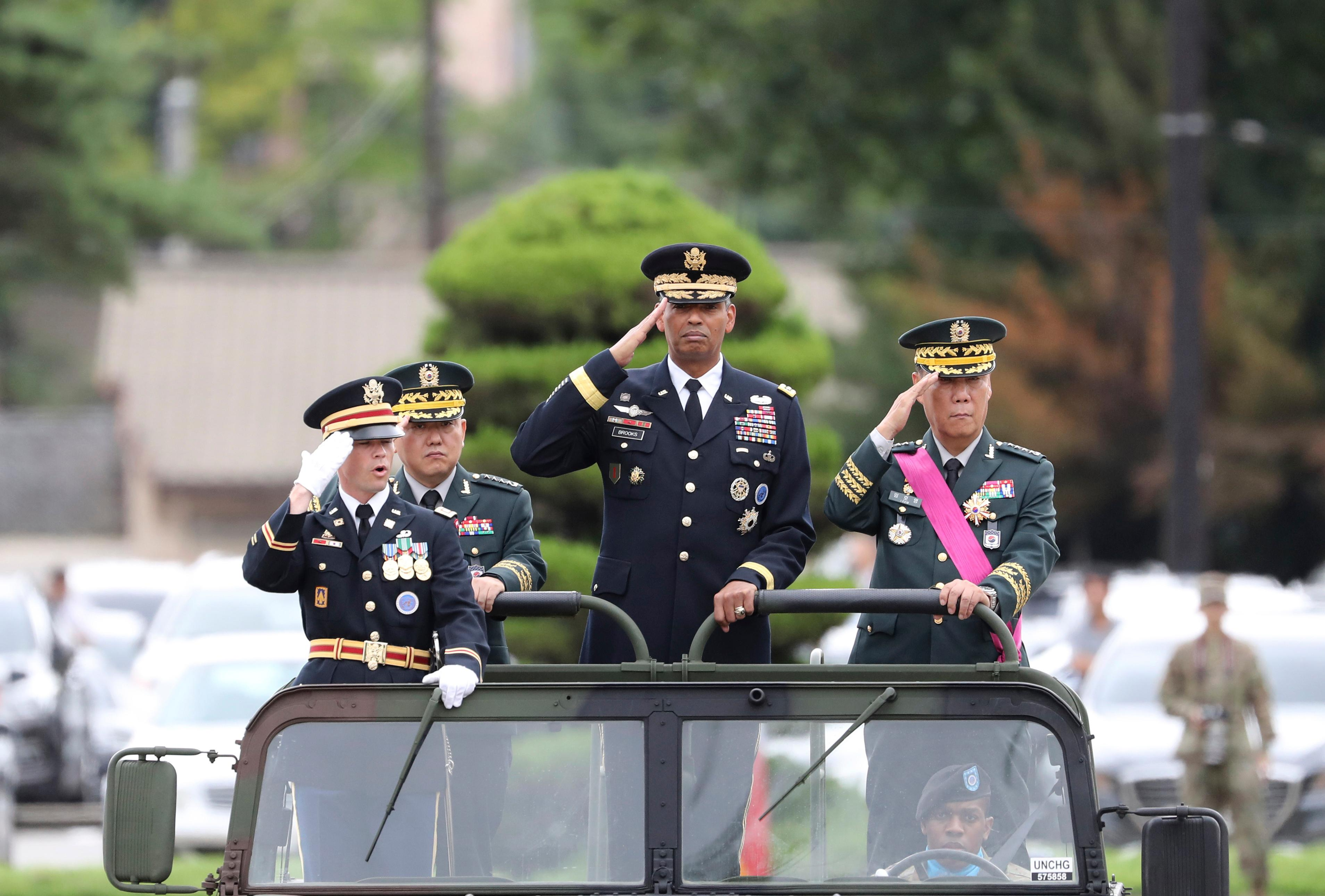 U.S. Gen. Vincent Brooks, commander of Combined Forces Command, center, salutes with incoming Deputy Commander Gen. Kim Byung-joo, left rear, and outgoing Deputy Commander Gen. Leem Ho-young, right, in a car, as they inspect honor guards during a change of command and change of responsibility ceremony for Deputy Commander of the South Korea-U.S. Combined Force Command at Yongsan Garrison, a U.S. military base, in Seoul, South Korea, Friday, Aug. 11, 2017. U.S. and South Korean military officials plan to move ahead with large-scale exercises later this month that North Korea, now finalizing plans to launch a salvo of missiles toward Guam, claims are a rehearsal for war. (AP Photo/Lee Jin-man)