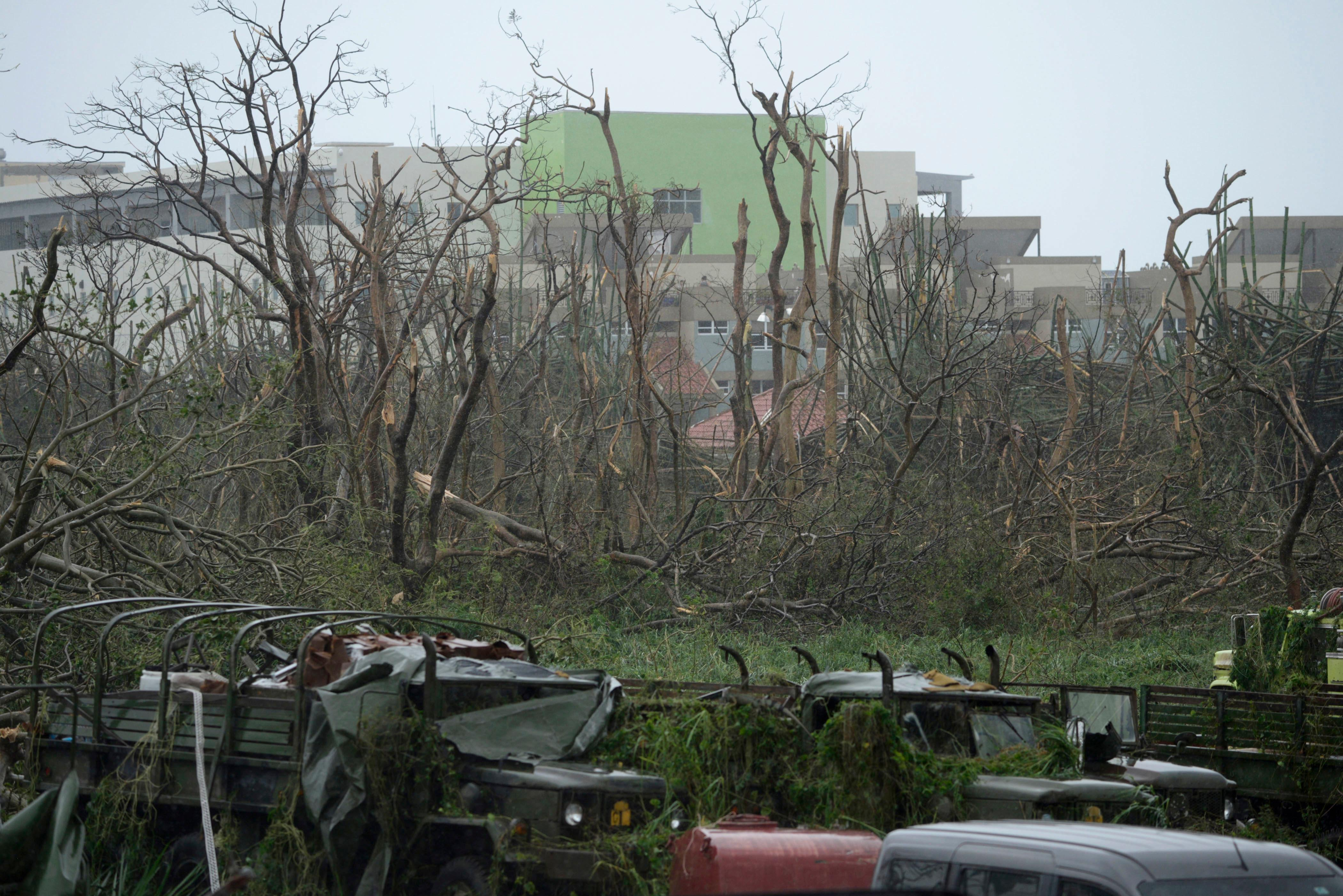 CORRECTS TO REMOVE REFERENCE OF HURRICANE CATEGORY - Trees stripped of their foliage and damaged trucks stand at the principal entrance at the Emergency Management Agency during the impact of Hurricane Maria, which hit the eastern region of the island, in Humacao, Puerto Rico, Wednesday, Sept. 20, 2017. The U.S. National Hurricane Center says Maria has lost its major hurricane status, after raking Puerto Rico. But forecasters say some strengthening is in the forecast and Maria could again become a major hurricane by Thursday. (AP Photo/Carlos Giusti)