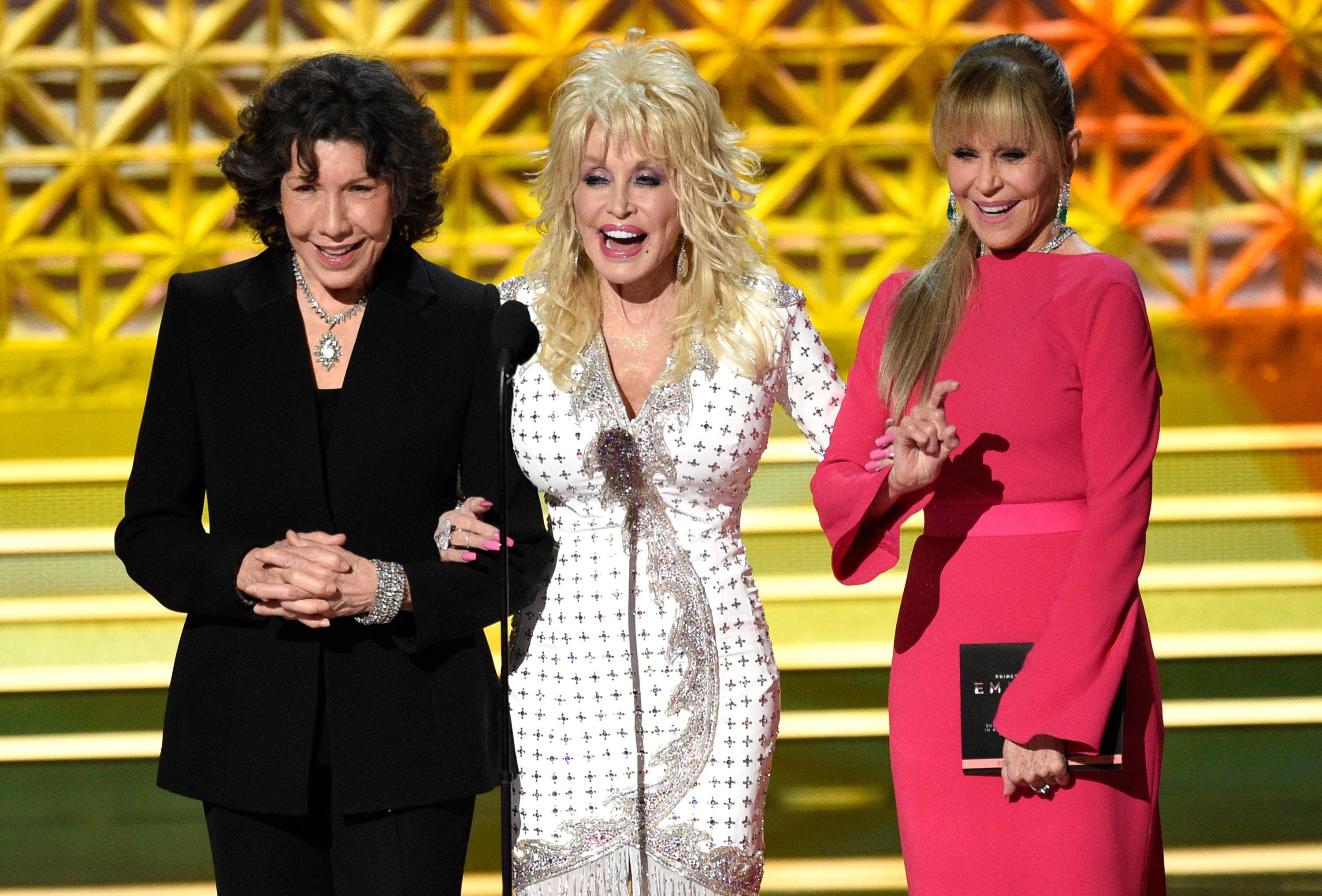 Lily Tomlin, from left, Dolly Parton and Jane Fonda present the award for outstanding supporting actor in a limited series or a movie at the 69th Primetime Emmy Awards on Sunday, Sept. 17, 2017, at the Microsoft Theater in Los Angeles. (Photo by Chris Pizzello/Invision/AP)