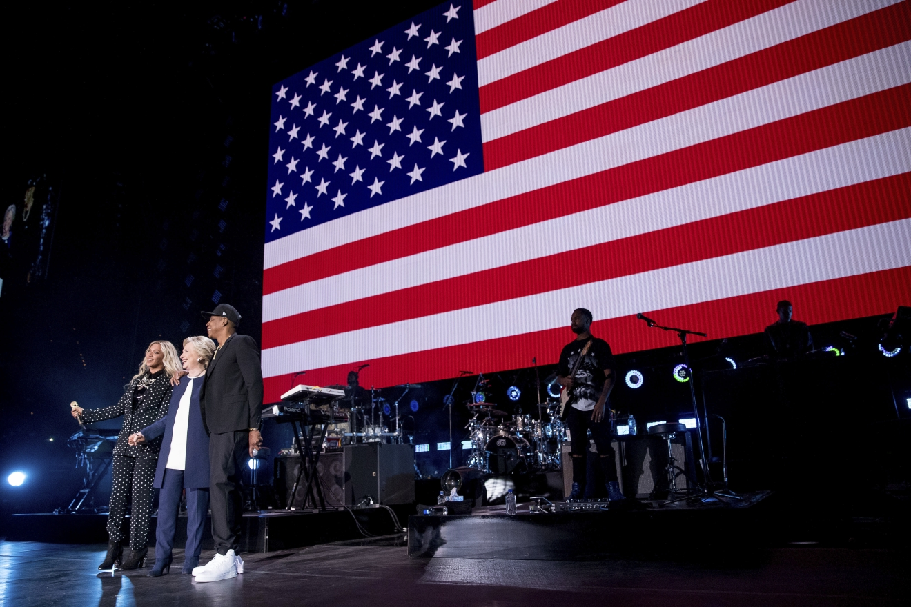 Democratic presidential candidate Hillary Clinton, second from left, appears on stage with artists Jay Z, right, and Beyonce, left, during a free concert at at the Wolstein Center in Cleveland, Friday, Nov. 4, 2016. (AP Photo/Andrew Harnik)