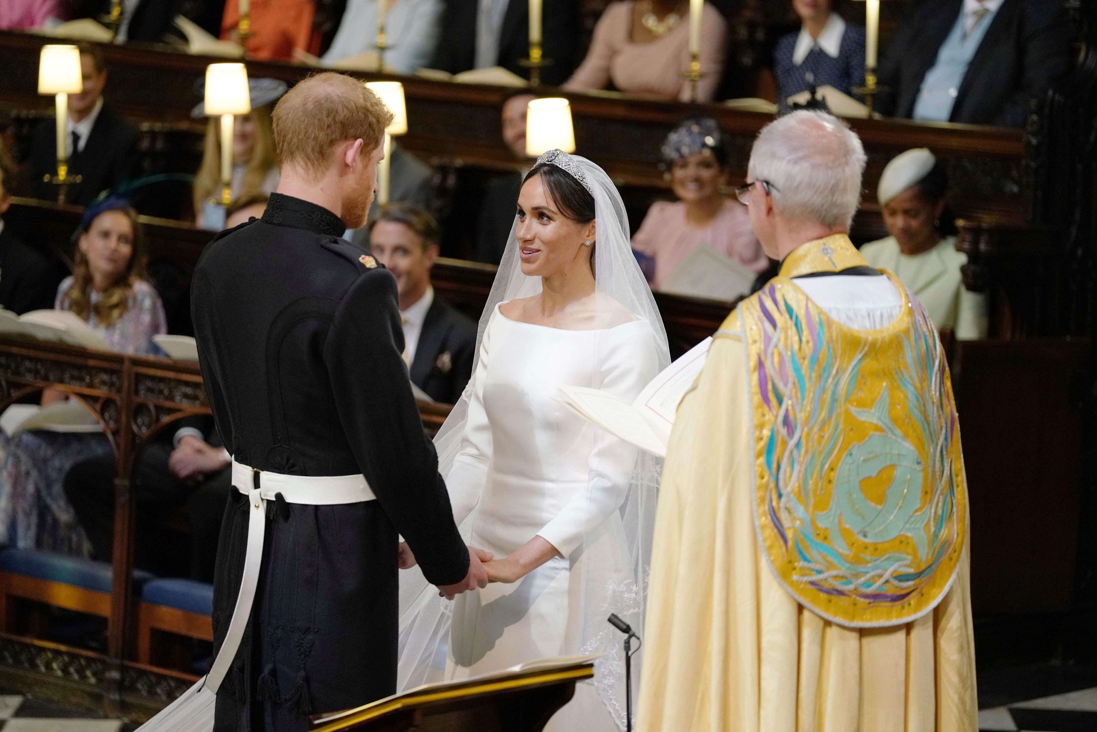 Britain's Prince Harry and Meghan Markle hold hands during their wedding ceremony oin St. George's Chapel in Windsor Castle in Windsor, near London, England, Saturday, May 19, 2018. (Dominic Lipinski/pool photo via AP)