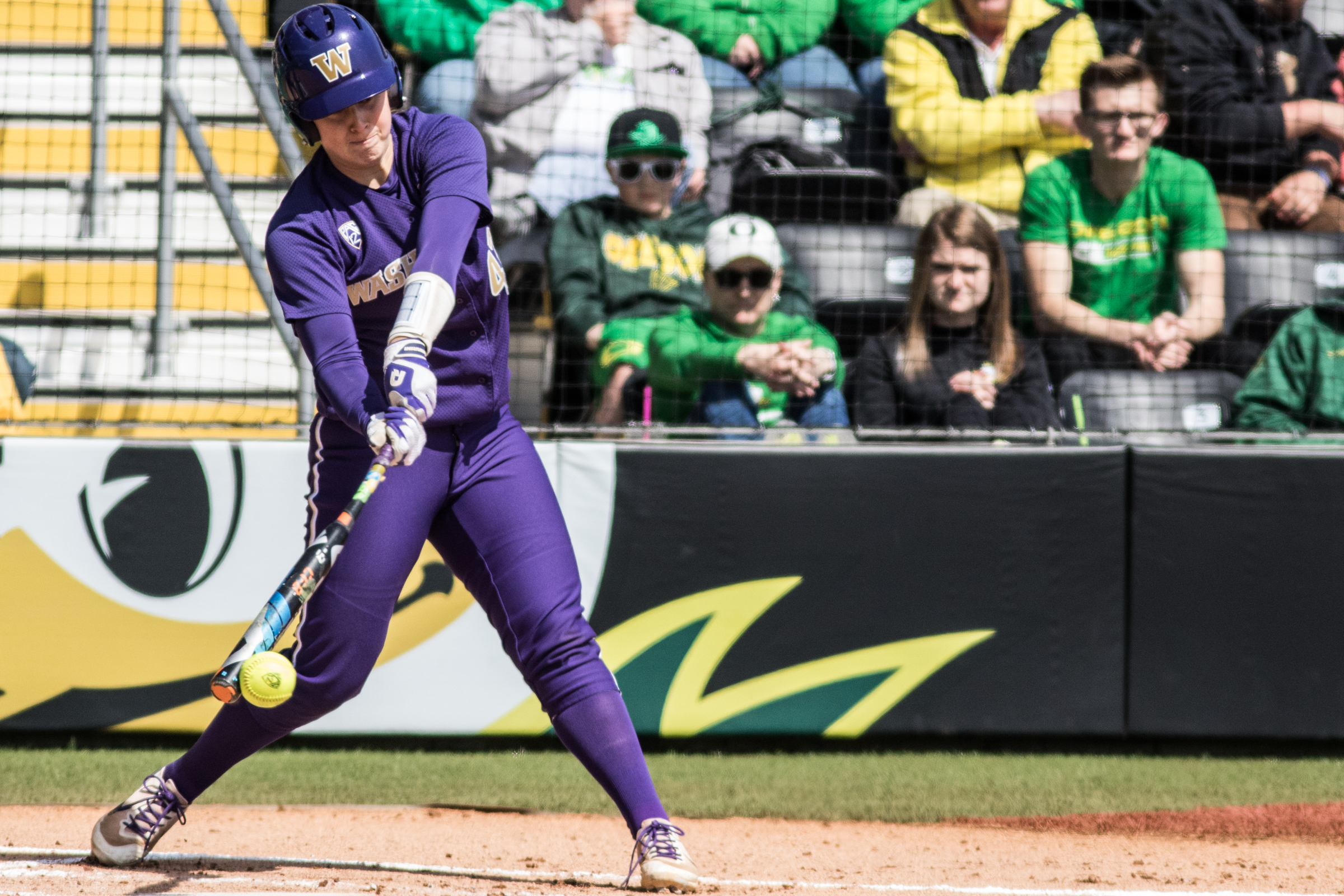 Washington Huskies catcher Morganne Flores (#47) makes contact with a pitch. In the final game of a three-game series, the University of Washington Huskies defeated the Oregon Ducks 5-3.  The Ducks led through the bottom of the 7th inning, but Washington's Morganne Flores (#47) tied it up with a two-run double.  Flores drove in two more runs in the 9th to take the lead.  Photo by Austin Hicks, Oregon News Lab