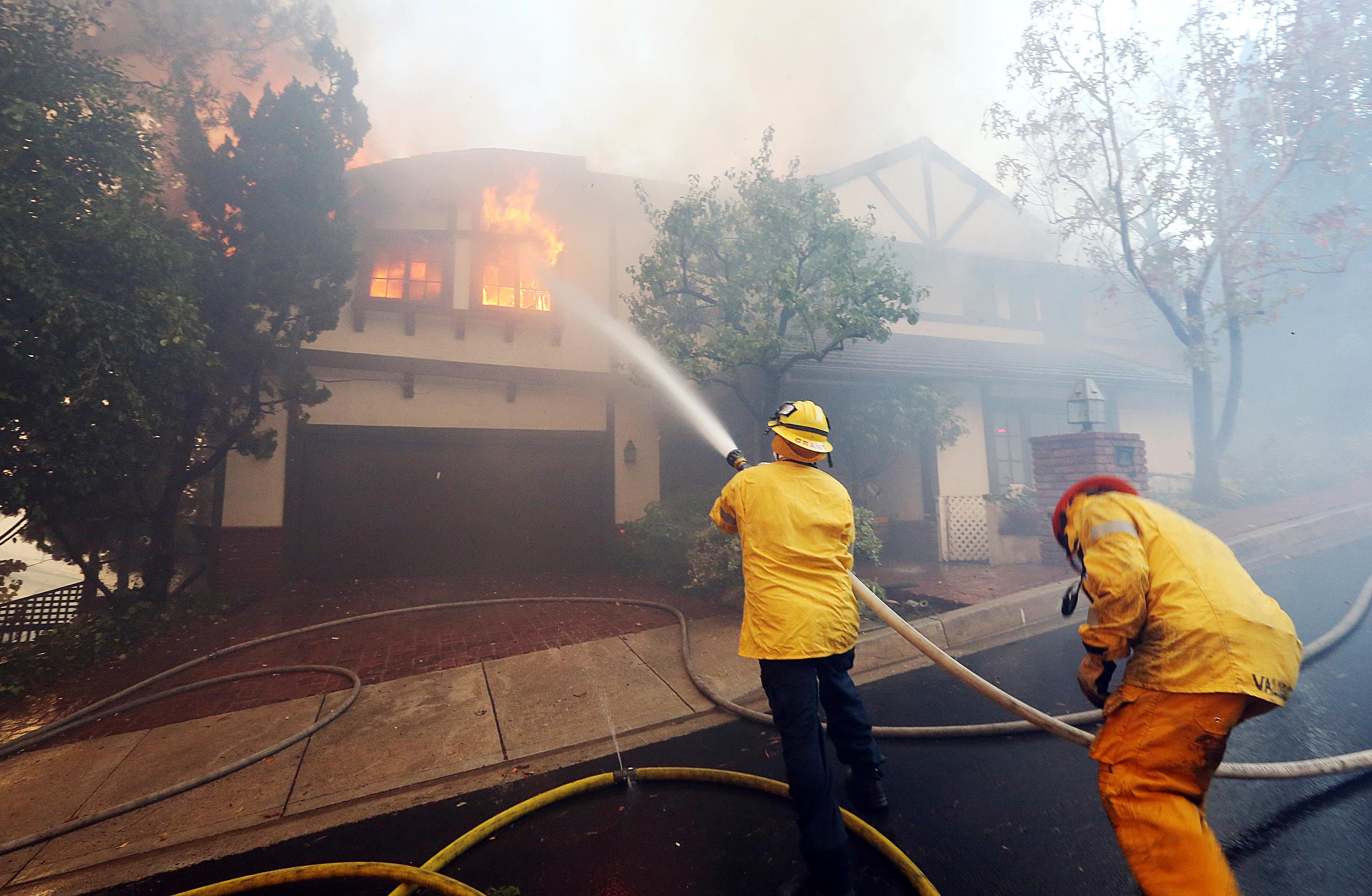 Los Angeles firefighters battle to contain flames to a burning home and prevent the fire's spread to adjoining properties in the Bel Air district of Los Angeles on Wednesday, Dec. 6, 2017. (AP Photo/Reed Saxon)
