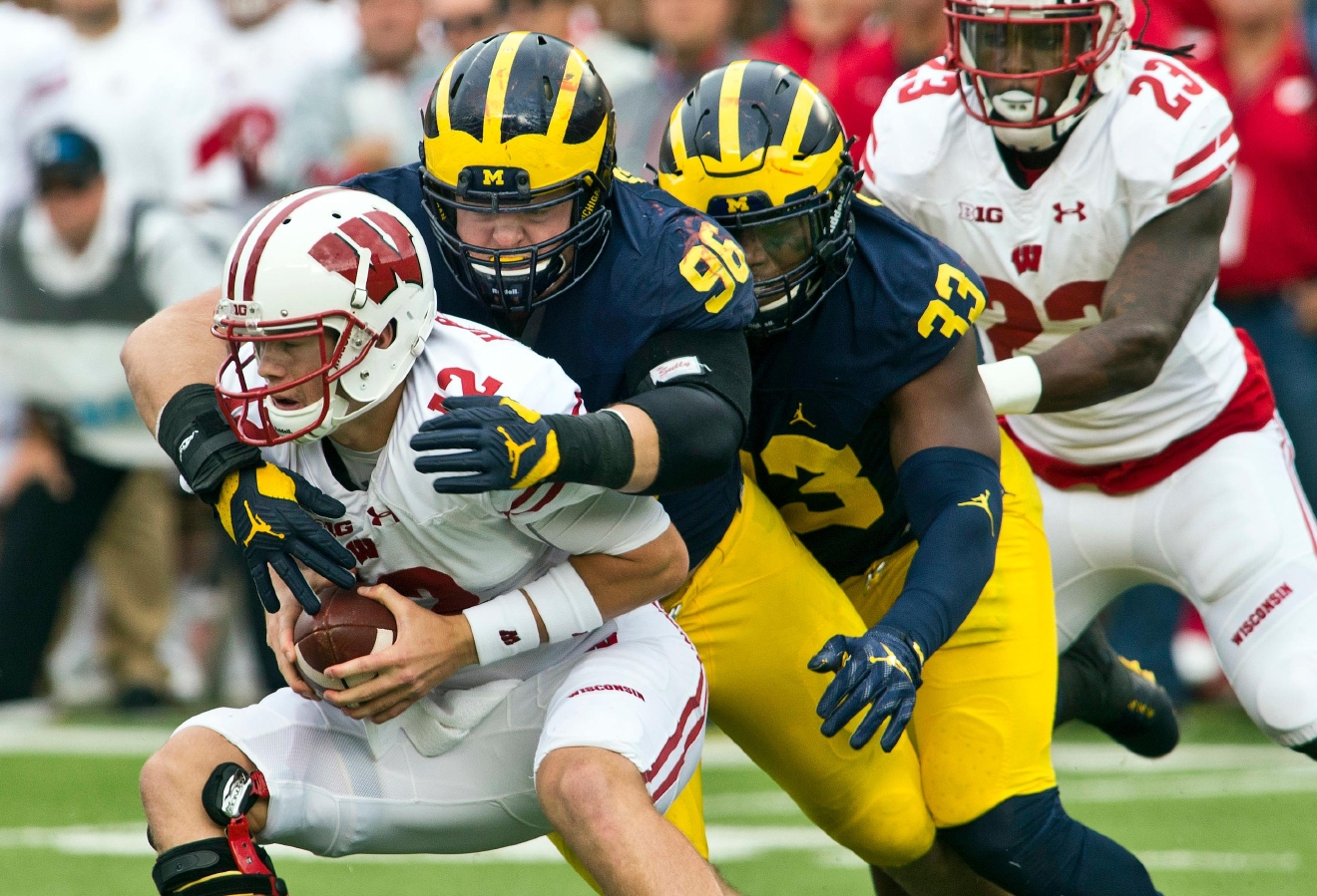 Wisconsin quarterback Alex Hornibrook (12) is sacked by Michigan defensive tackle Ryan Glasgow (96) and defensive end Taco Charlton (33) in the second quarter of an NCAA college football game at Michigan Stadium in Ann Arbor, Mich., Saturday, Oct. 1, 2016. (AP Photo/Tony Ding)