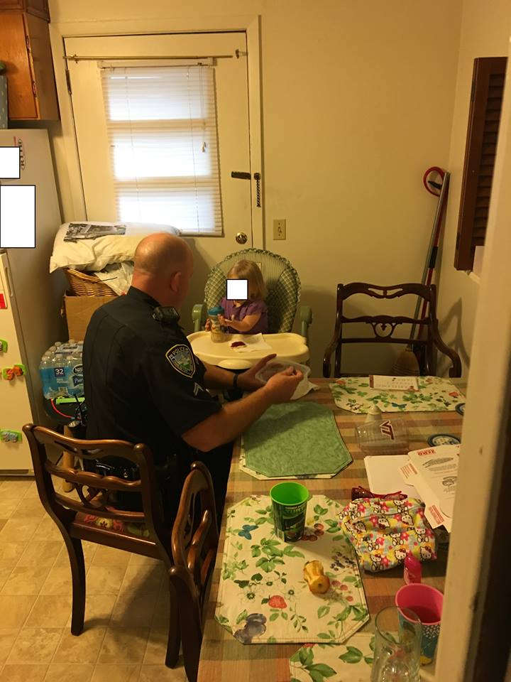 Charleston Police Cpl. Martin McMicken feeds a 2-year-old child whom police say they found home alone. (Charleston Police Department)