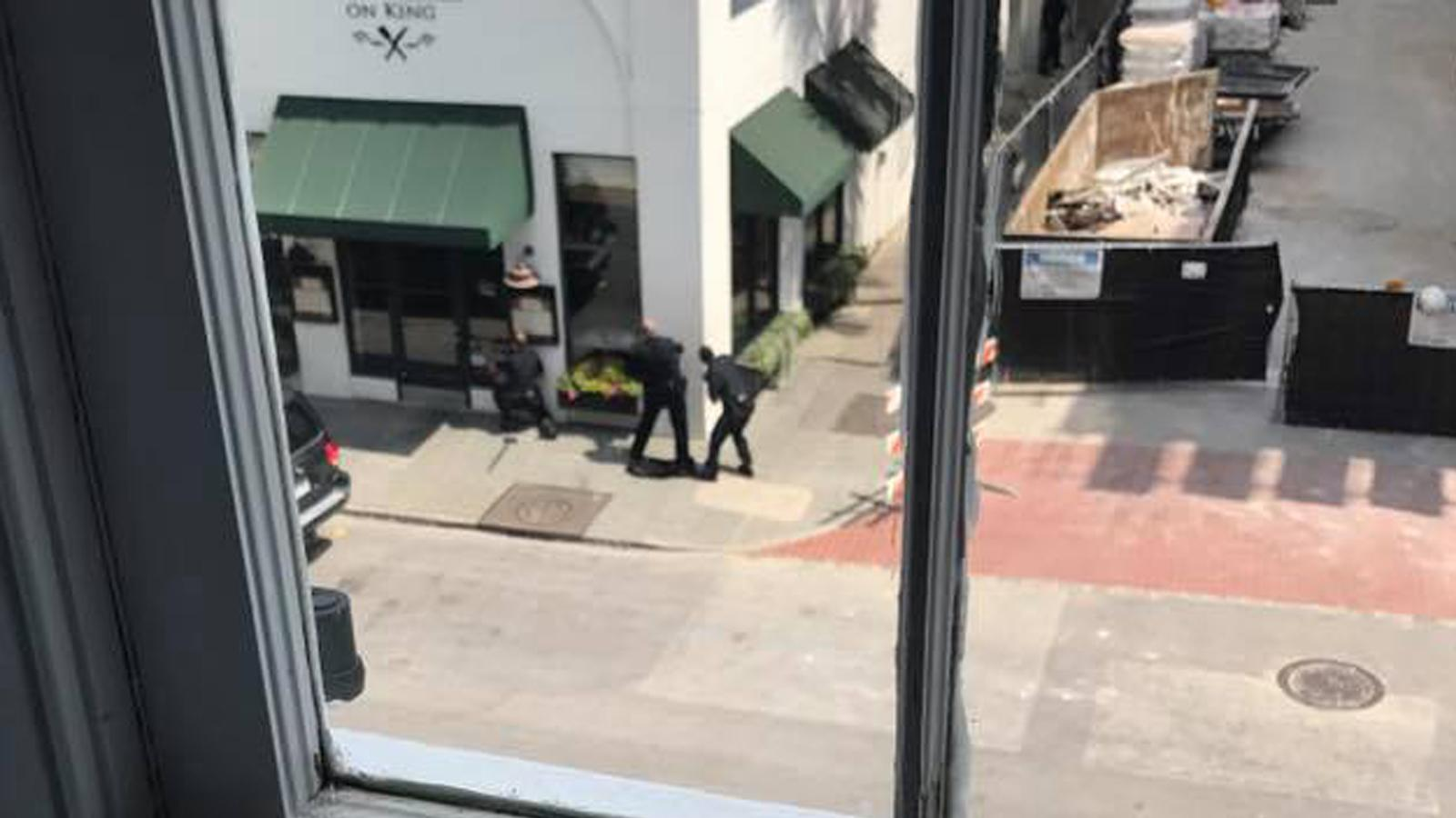 Police officers with weapons drawn outside Virginia's on King restaurant. (Provided/Robbie Kimbrough)
