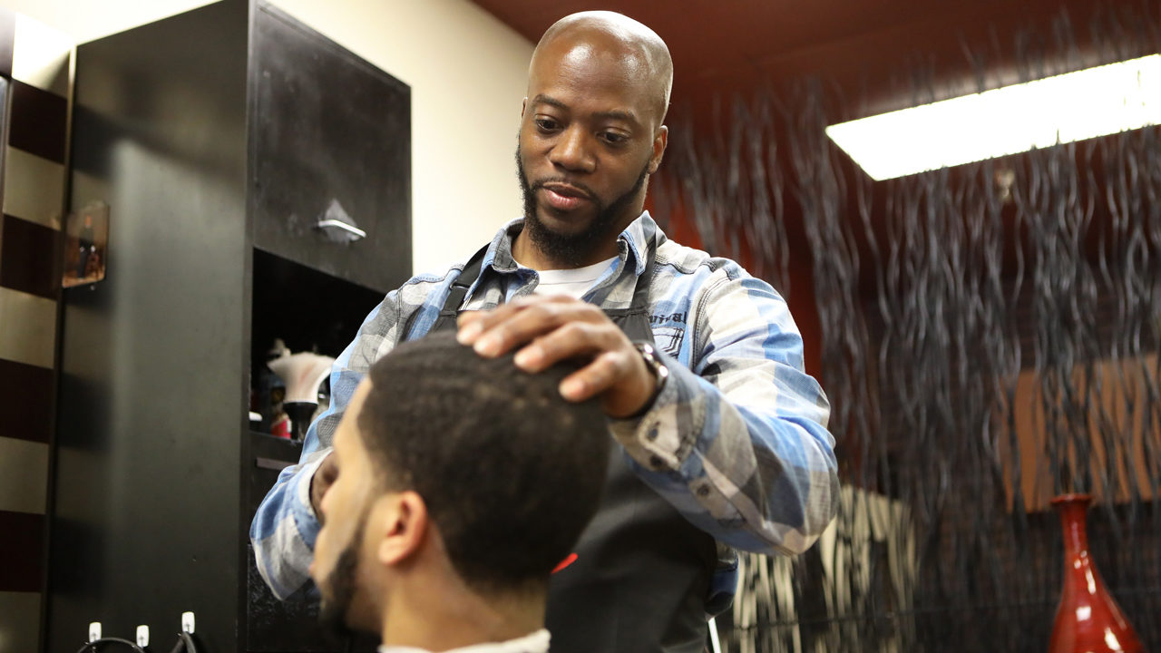 Brian Britt cuts the hair of DeUndre Moore at the Inspire Barber and Beauty Salon, which he owns, in Madison, Wis., on May 8, 2019. Britt opened the salon in 2017 and said he had difficulty finding a space to rent due to having a number of convictions on his record, including possession with intent to deliver marijuana in 2000.