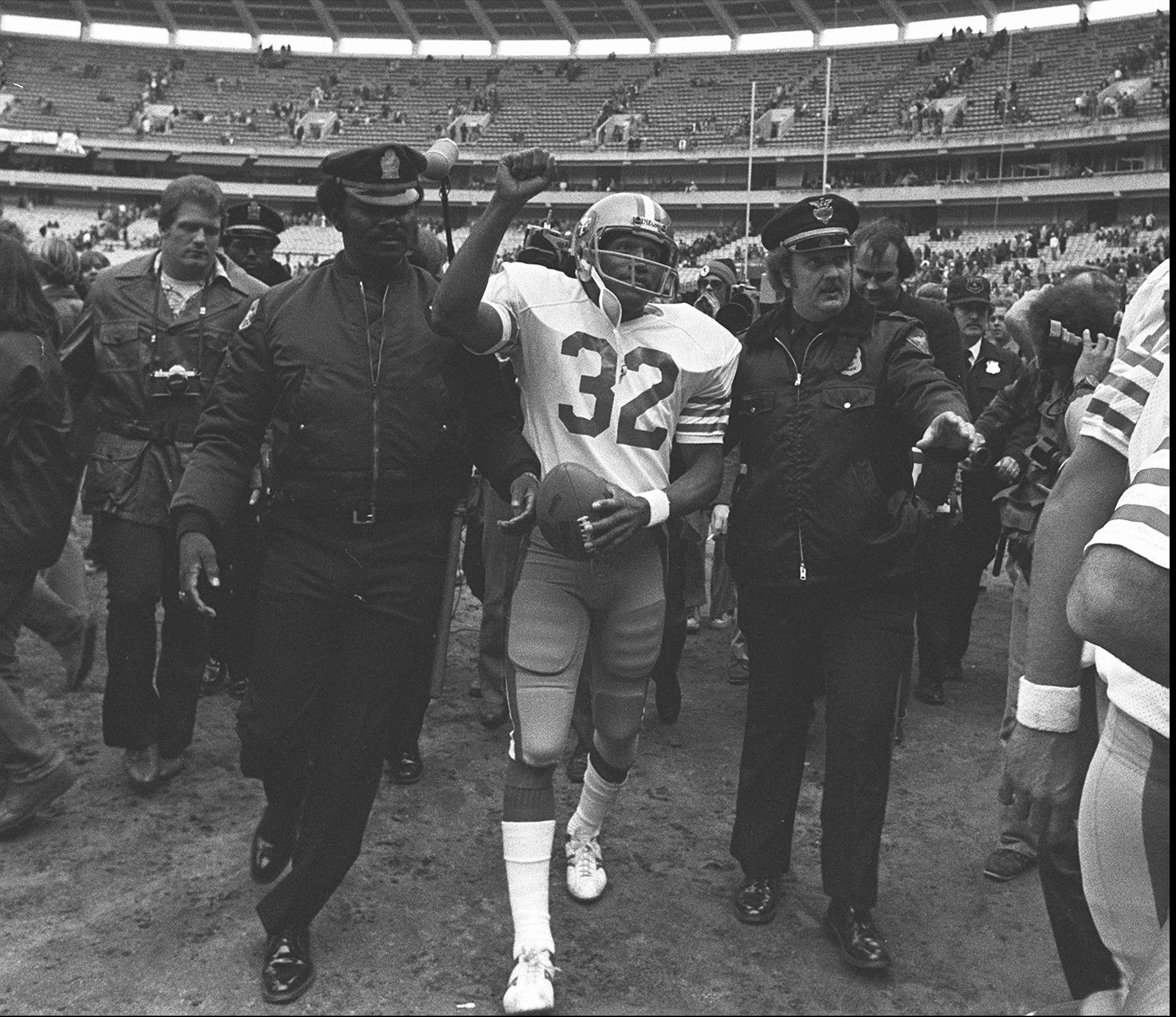FILE - In this Dec. 16, 1979 file photo, San Francisco 49ers running back O.J. Simpson is escorted from the field by police after the final NFL football game of his career against in the Atlanta Falcons at Atlanta Fulton County Stadium in Atlanta, Ga. Simpson retired from football after the 1979 season, later being inducted into the Pro Football Hall of Fame and beginning careers in acting and football broadcasting. A Nevada prison official said early Sunday, Oct. 1, 2017, O.J. Simpson, the former football legend and Hollywood star, has been released from a Nevada prison in Lovelock after serving nine years for armed robbery.  (AP Photo, File)