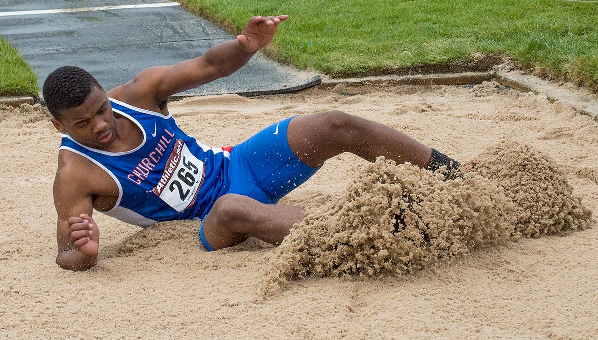 "Churchill High School's Samuel Jackson slides into first place in the 5A-3 Midwestern League District Championship Triple Jump event with a mark of 45'1"". Photo by Emily Gonzalez, Oregon News Lab."