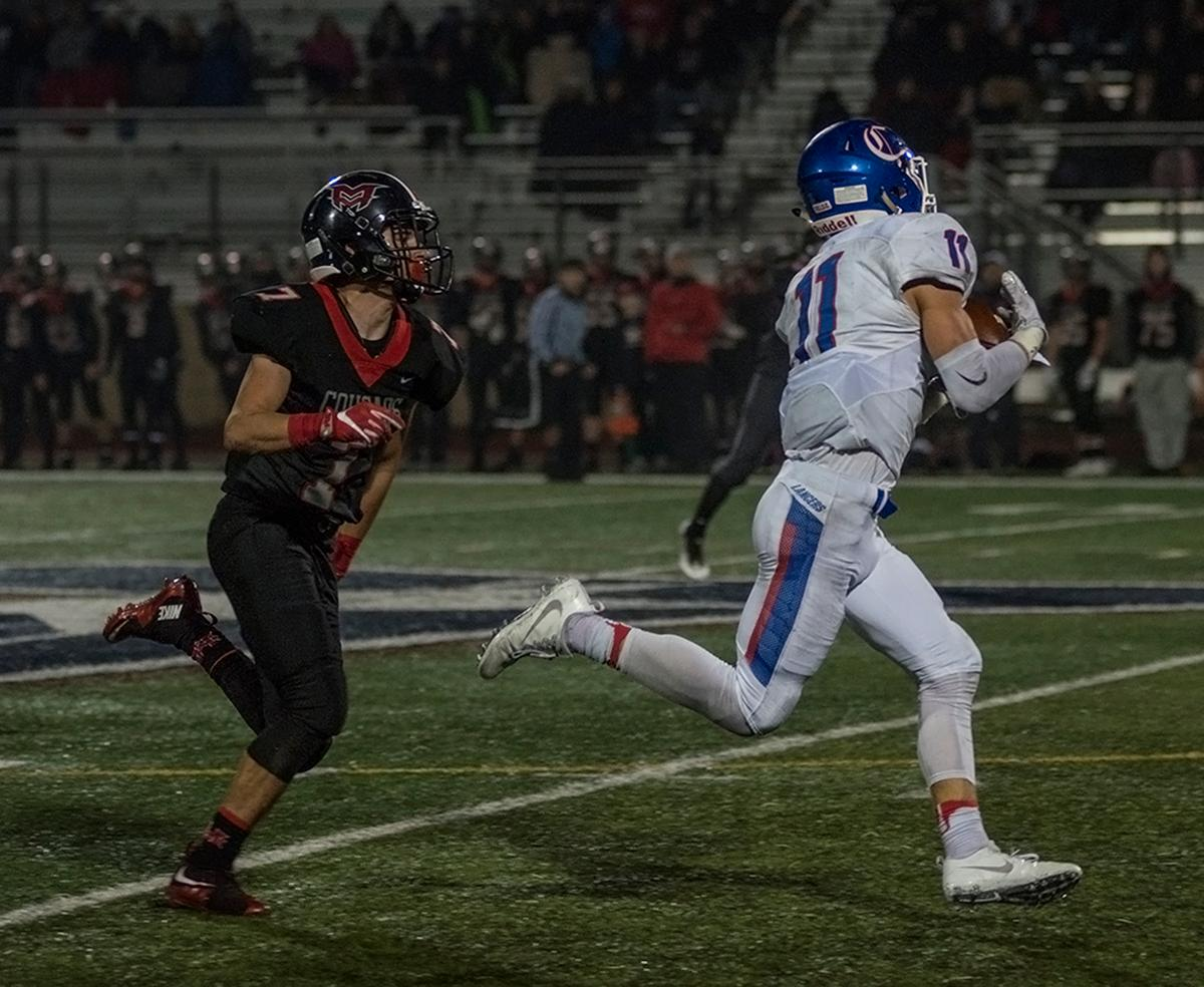 Churchill Lancers wide receiver Lucas Schwinn (#11) runs away with the ball for a touchdown. The Churchill Lancers defeated the Mountain View Cougars 35-28 on Saturday night at Liberty High School, securing a spot in the 5A state championship. Photo by Abigail Winn, Oregon News Lab