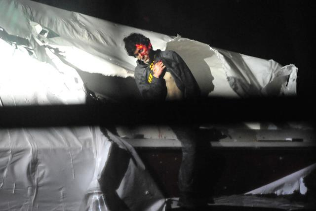 A bloody Tsarnaev emerges from the boat and surrenders