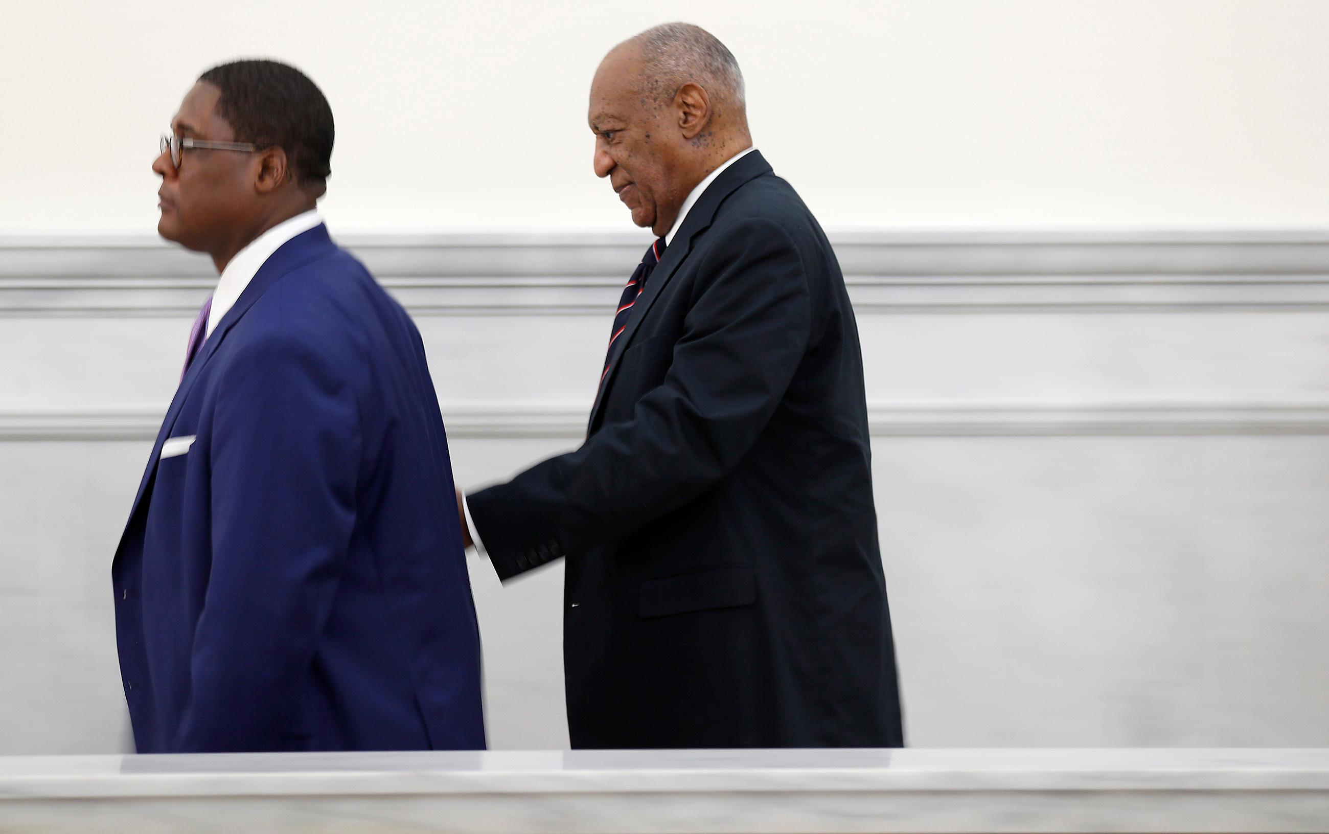 Andrew Wyatt, left, leads Bill Cosby, right, back to the courtroom at the Montgomery County Courthouse during Cosby's sexual assault trial in Norristown, Pa., Monday, June 12, 2017. (David Maialetti/The Philadelphia Inquirer via AP, Pool)