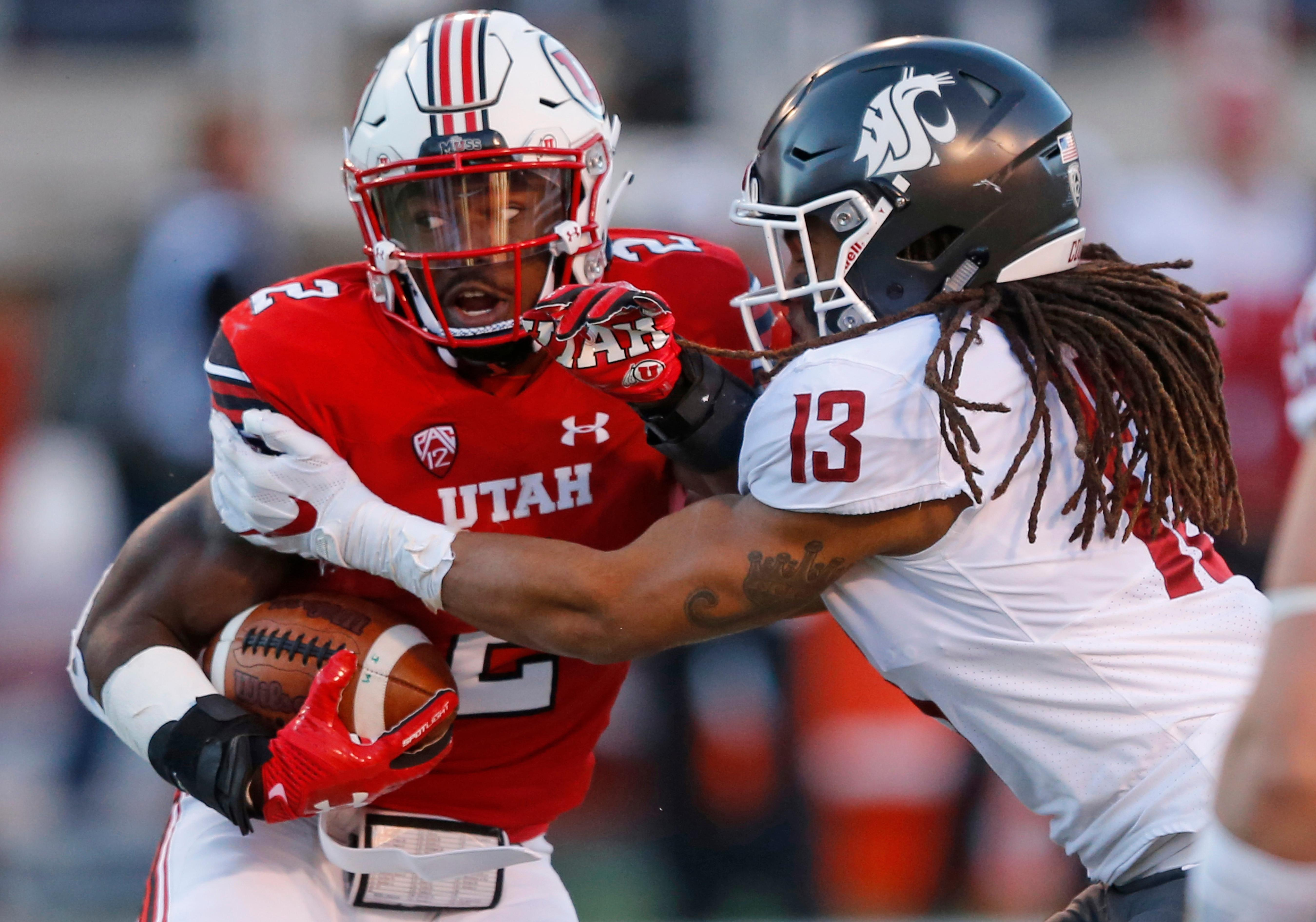 Utah running back Zack Moss (2) is tackled by Washington State linebacker Jahad Woods (13) in the first half during an NCAA college football game, Saturday, Nov. 11, 2017, in Salt Lake City. (AP Photo/Rick Bowmer)