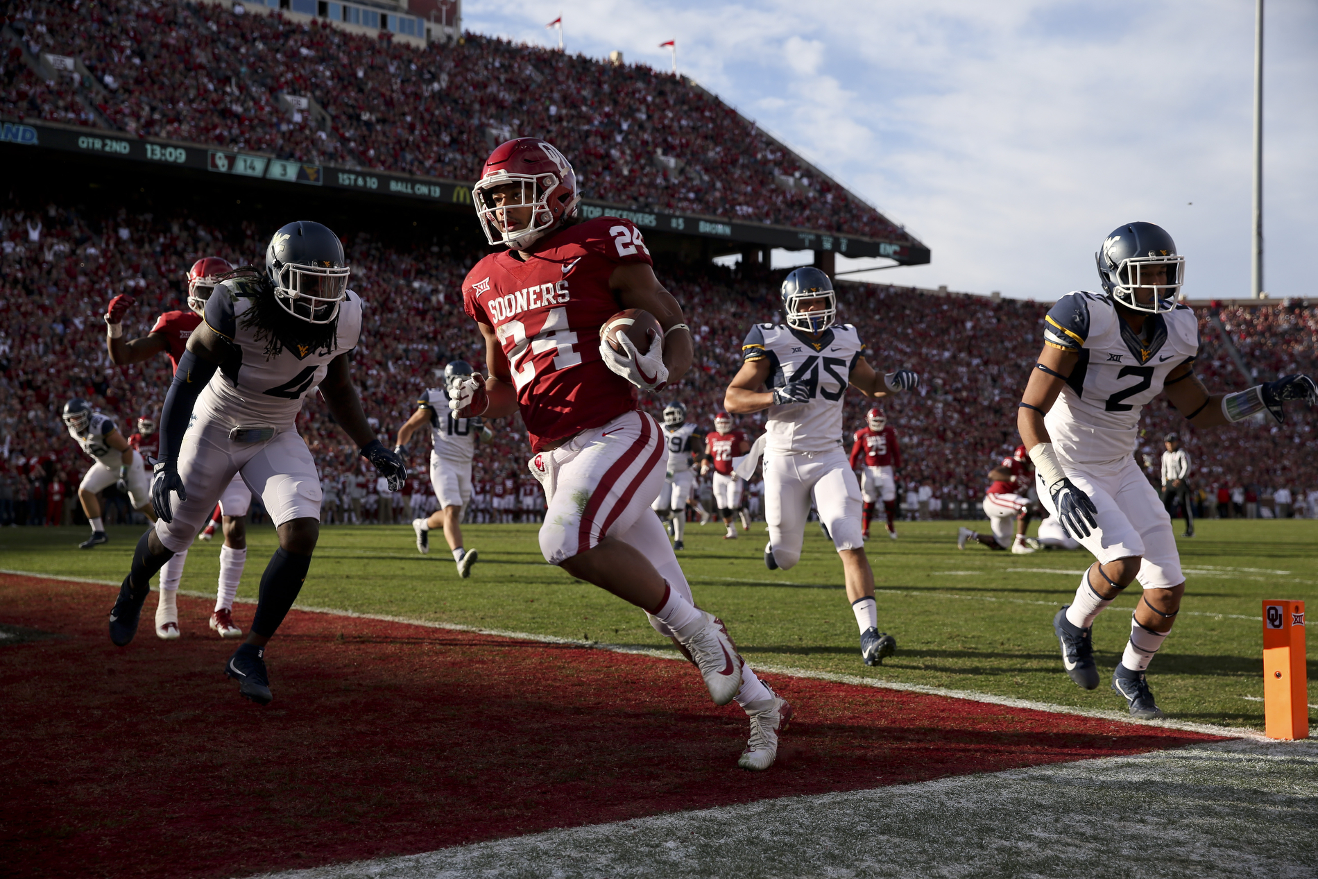 Oklahoma running back Rodney Anderson (24) runs passed West Virginia cornerback Mike Daniels Jr. (4), linebacker Adam Hensley (45) and safety Kenny Robinson (2) while scoring a touchdown during an NCAA college football game in Norman, Okla., Saturday, Nov. 25, 2017. (Ian Maule/Tulsa World via AP)