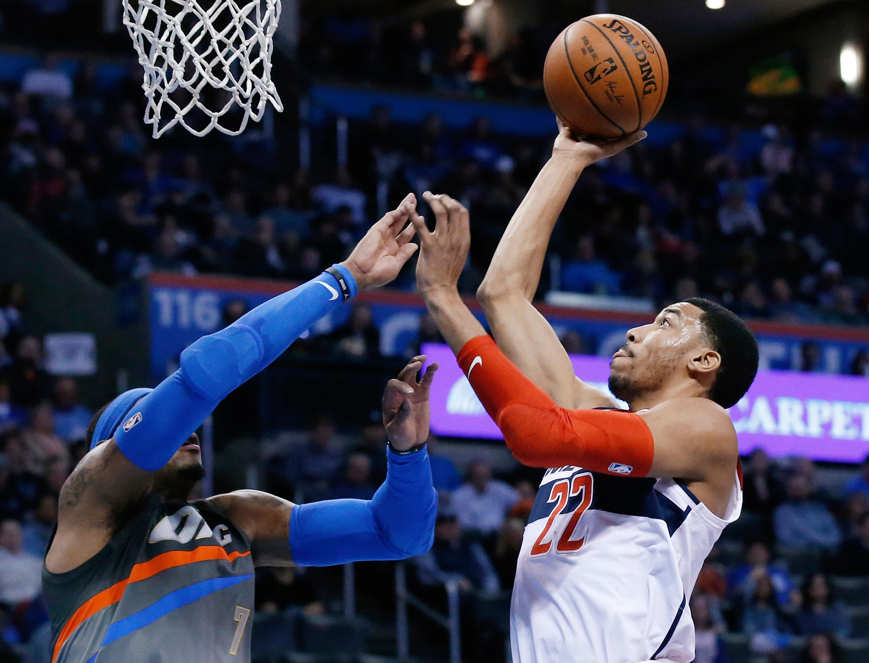 Washington Wizards forward Otto Porter Jr. (22) shoots over Oklahoma City Thunder forward Carmelo Anthony (7) during the first quarter of an NBA basketball game in Oklahoma City, Thursday, Jan. 25, 2018. (AP Photo/Sue Ogrocki)