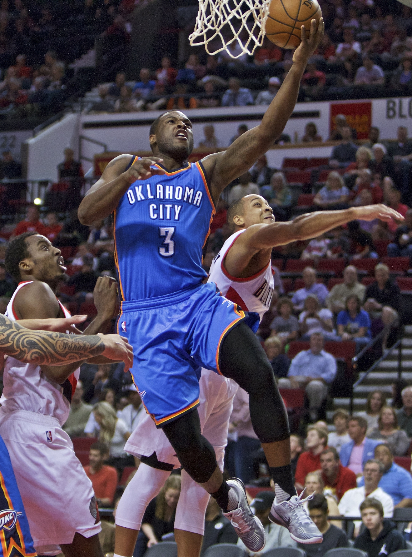 Oklahoma City Thunder guard Dion Waiters, center, shoots between Portland Trail Blazers guard C.J. McCollum, right, and forward Al-Farouq Aminu, left, during the first half of an NBA basketball game in Portland, Ore., Wednesday, April 6, 2016. (AP Photo/Craig Mitchelldyer)