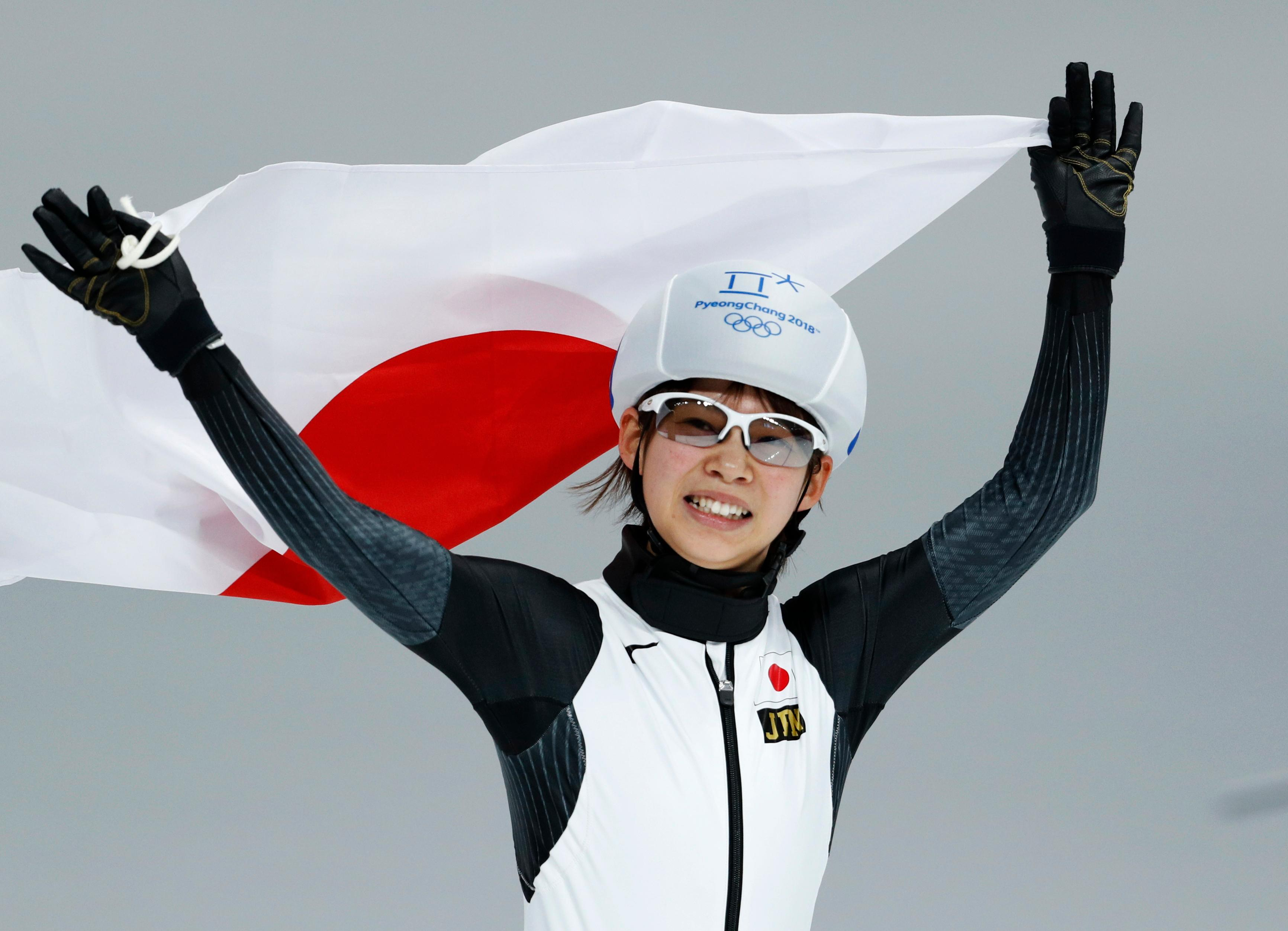 Gold medalist Nana Takagi of Japan celebrates with the national flag after the women's mass start final speedskating race at the Gangneung Oval at the 2018 Winter Olympics in Gangneung, South Korea, Saturday, Feb. 24, 2018. (AP Photo/John Locher)