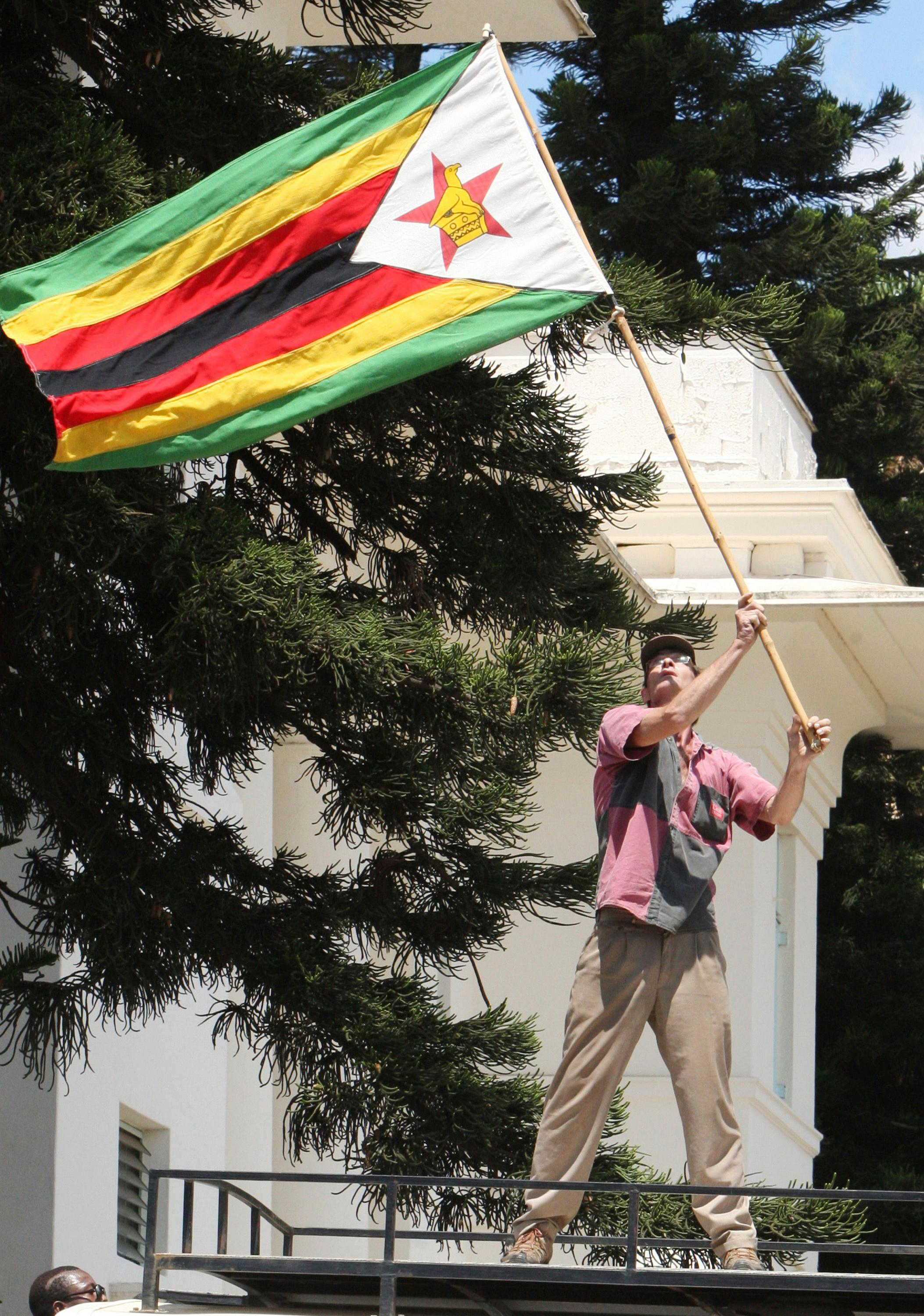 A man holds a Zimbabwe flag up as hundreds gather in Bulawayo, Zimbabwe, Saturday, Nov. 18, 2017 to demand the departure of President Robert Mugabe after nearly four decades in power. (AP Photo/Lucky Tshuma)