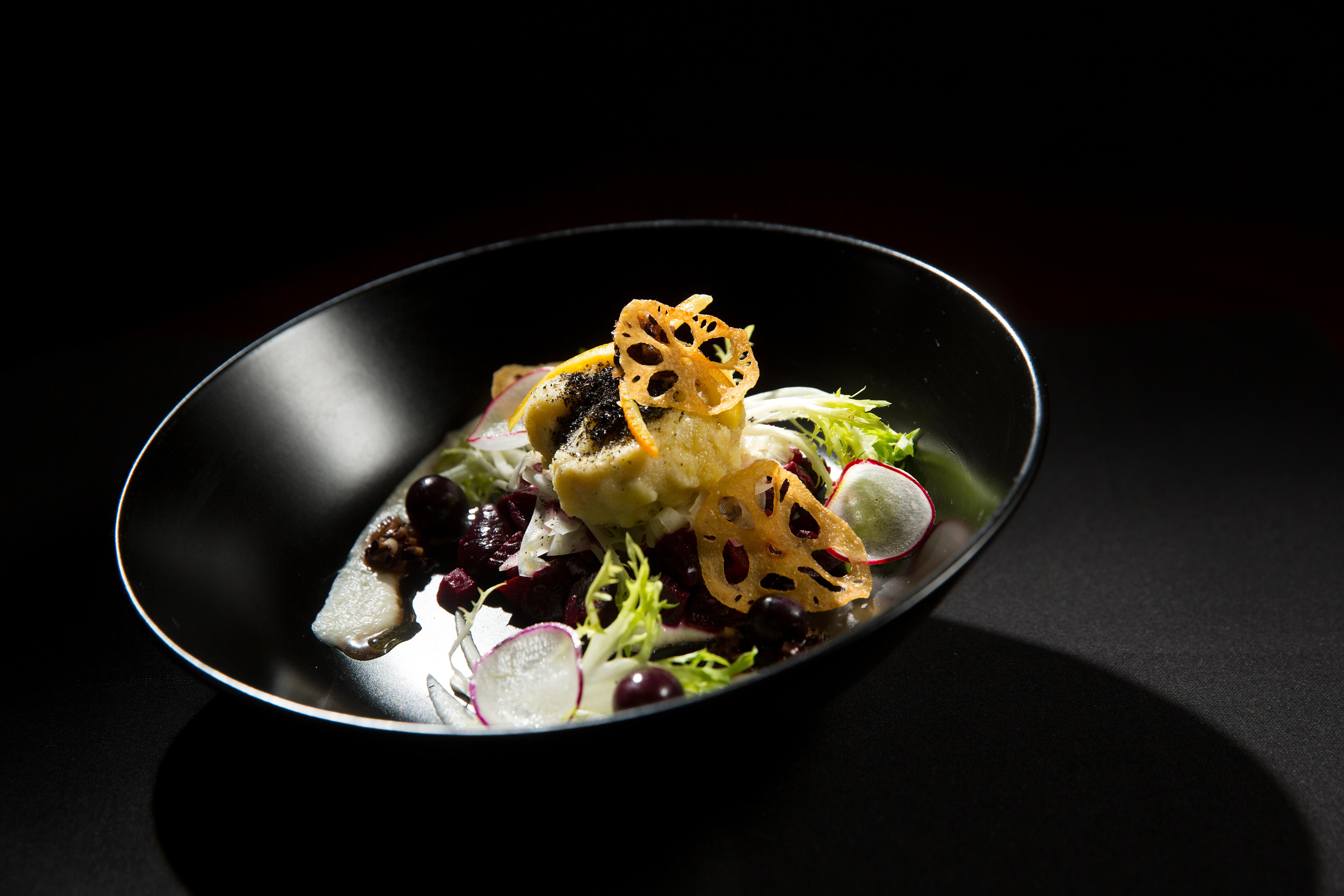 Owner and chef Derek Ronspies prepares Send Gnudes, a dish consisting of Willowood Farm marinated beets, blue cheese gnudi, cocoa nib vin, celeriac butter, pickled grapes, lotus root, green onion ash, and orange confit. Le Petit Cochon offers a menu that varies everyday. (Sy Bean / Seattle Refined)